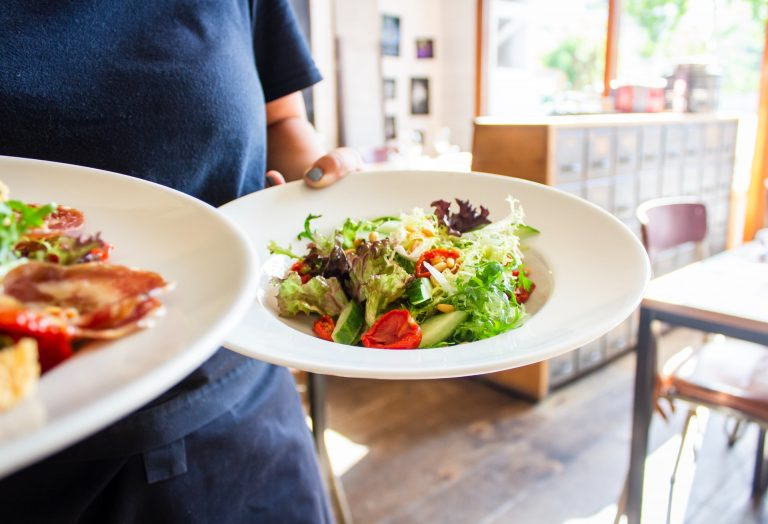 waitress carrying two bowls of salad with leafy greens and tomatoes and mixed veggies on top as a healthy food option