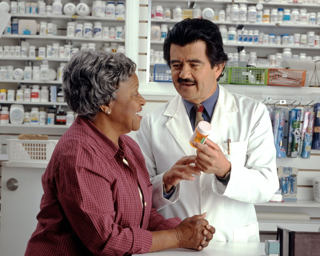 old black woman with hispanic pharmacist talking about medicine - talk to your doctor about hormones and breast cancer awareness