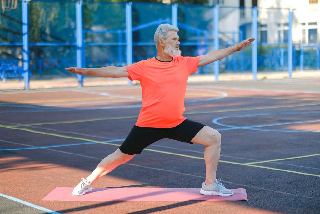 old white man in orange shirt doing yoga on a basketball court for exercise