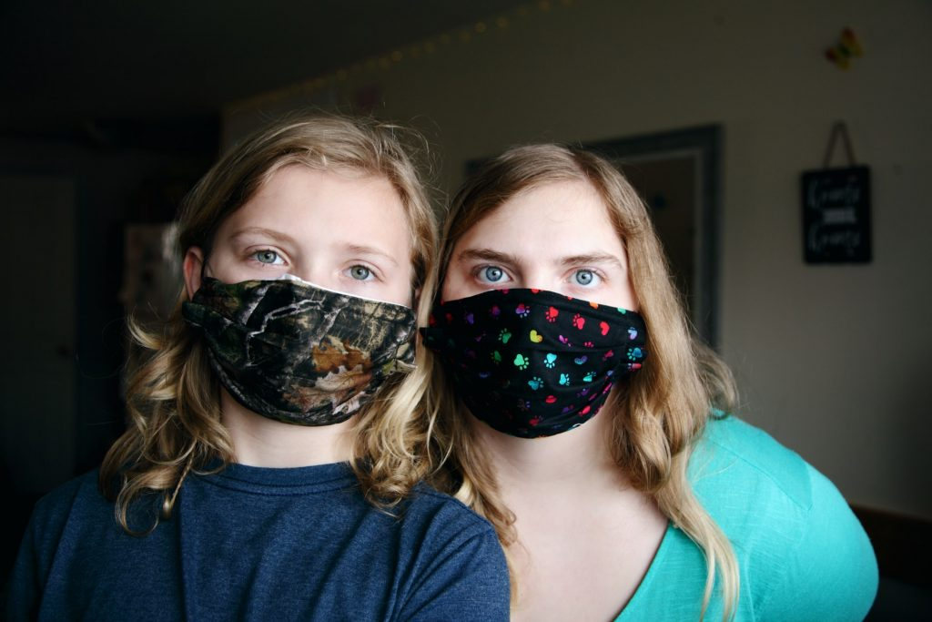 Mother daughter wear cloth masks per CDC guidelines. One mask with RealTree camo print and the other with paws and hearts to protect each other from COVID-19 pandemic