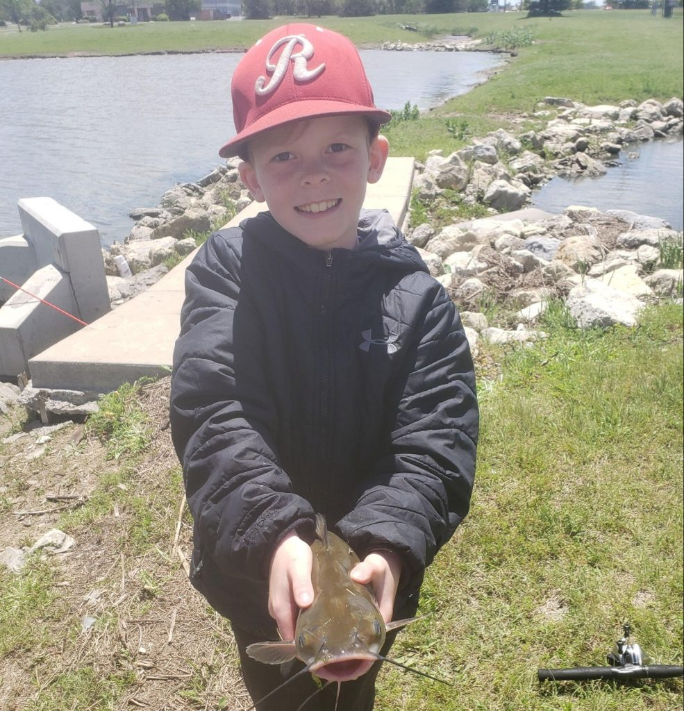 young white child with baby catfish in hands fishing at nmc health medical center fishing pond