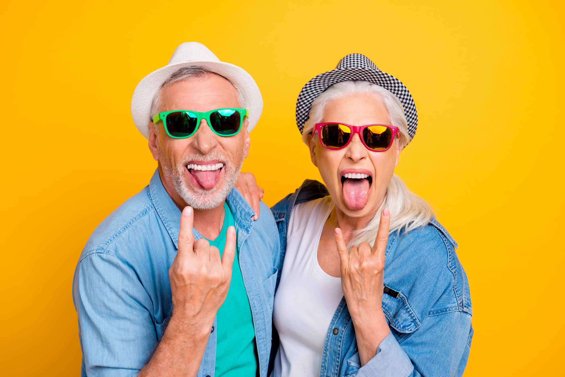 """elderly white man and elderly white woman sticking out tongue and holding up """"rock"""" on symbol"""
