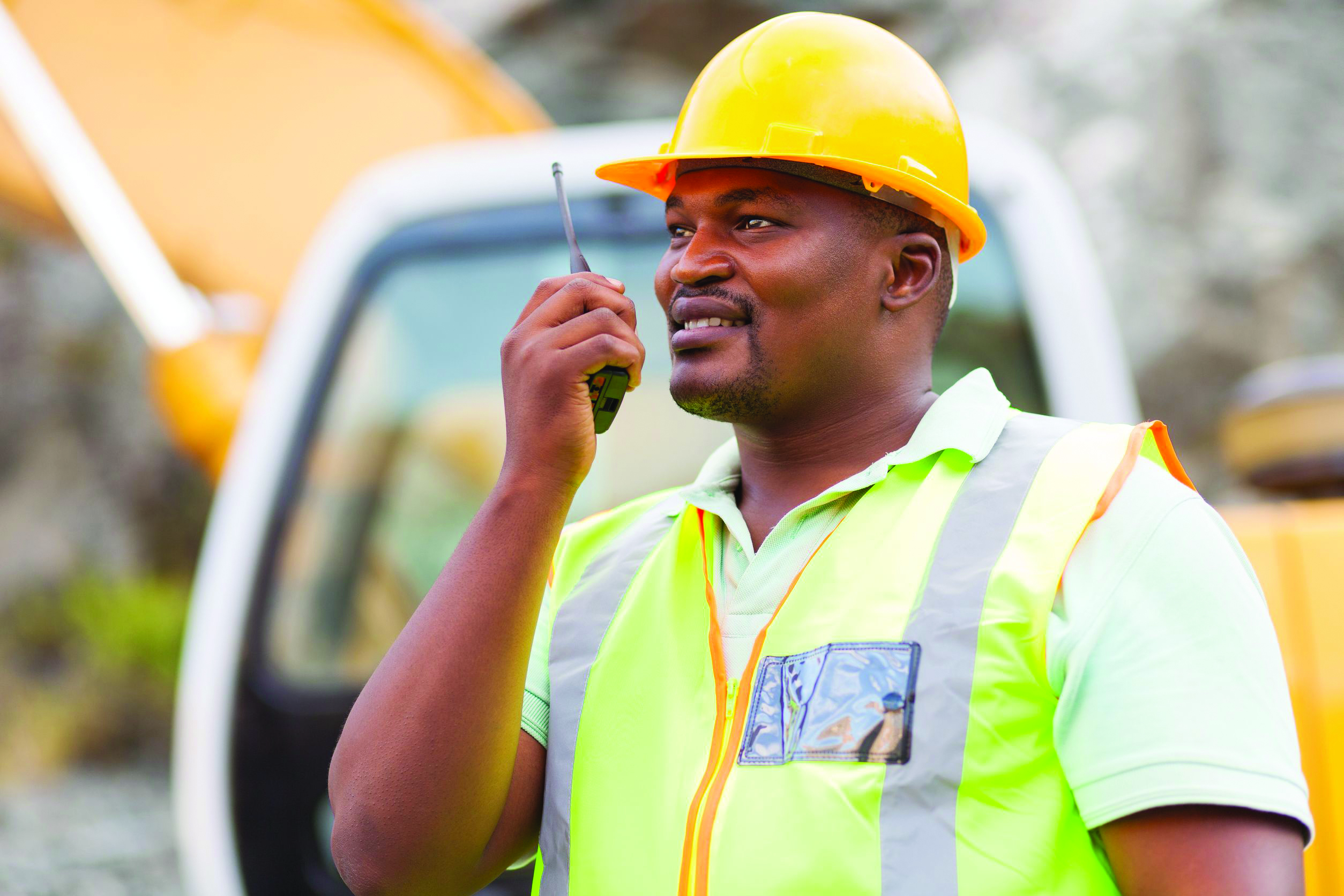 african american black man industrial worker talking on walkie-talkie at mining site
