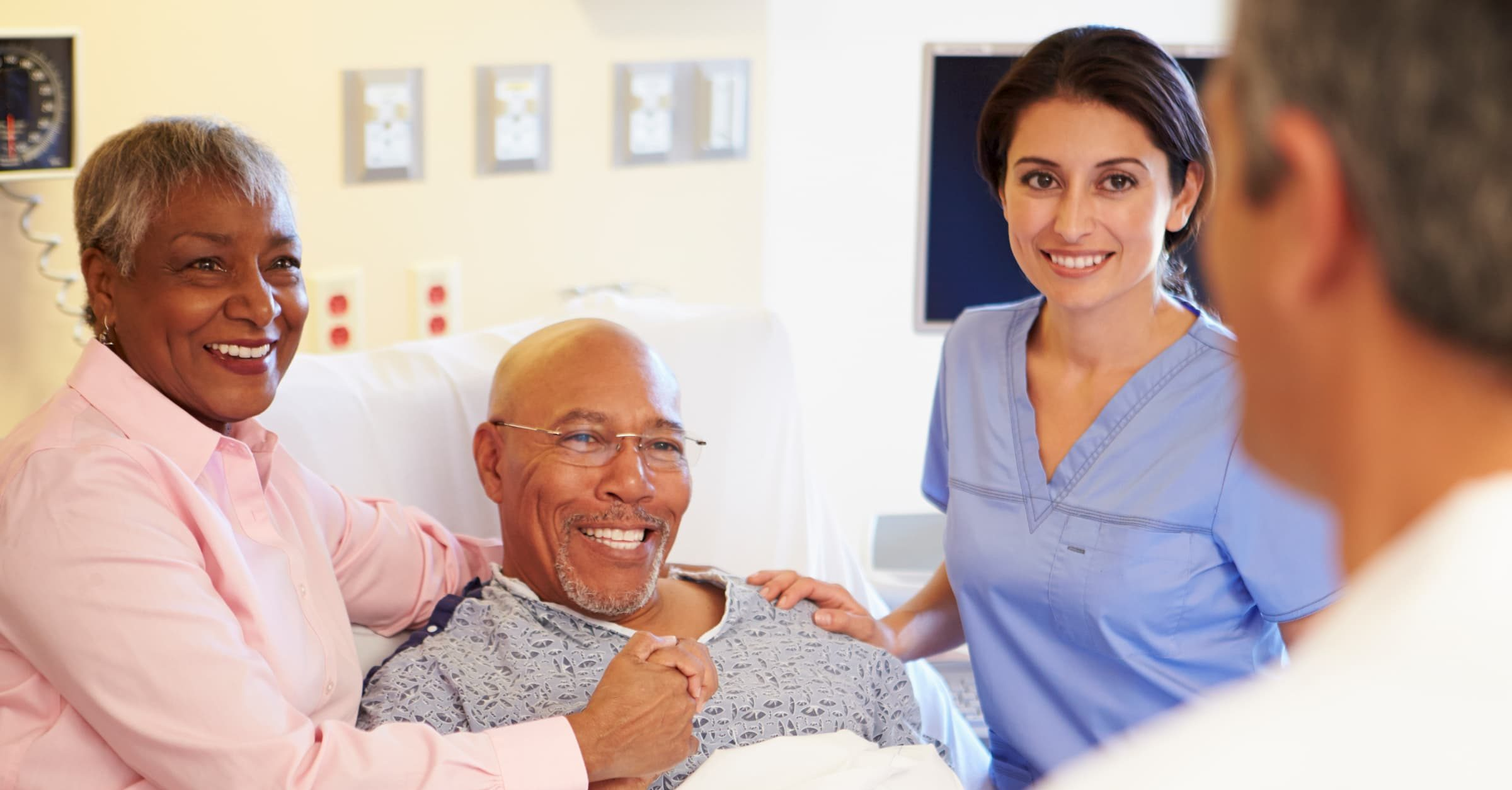 black woman hugging black man in hospital bed with nurse and doctor standing around them