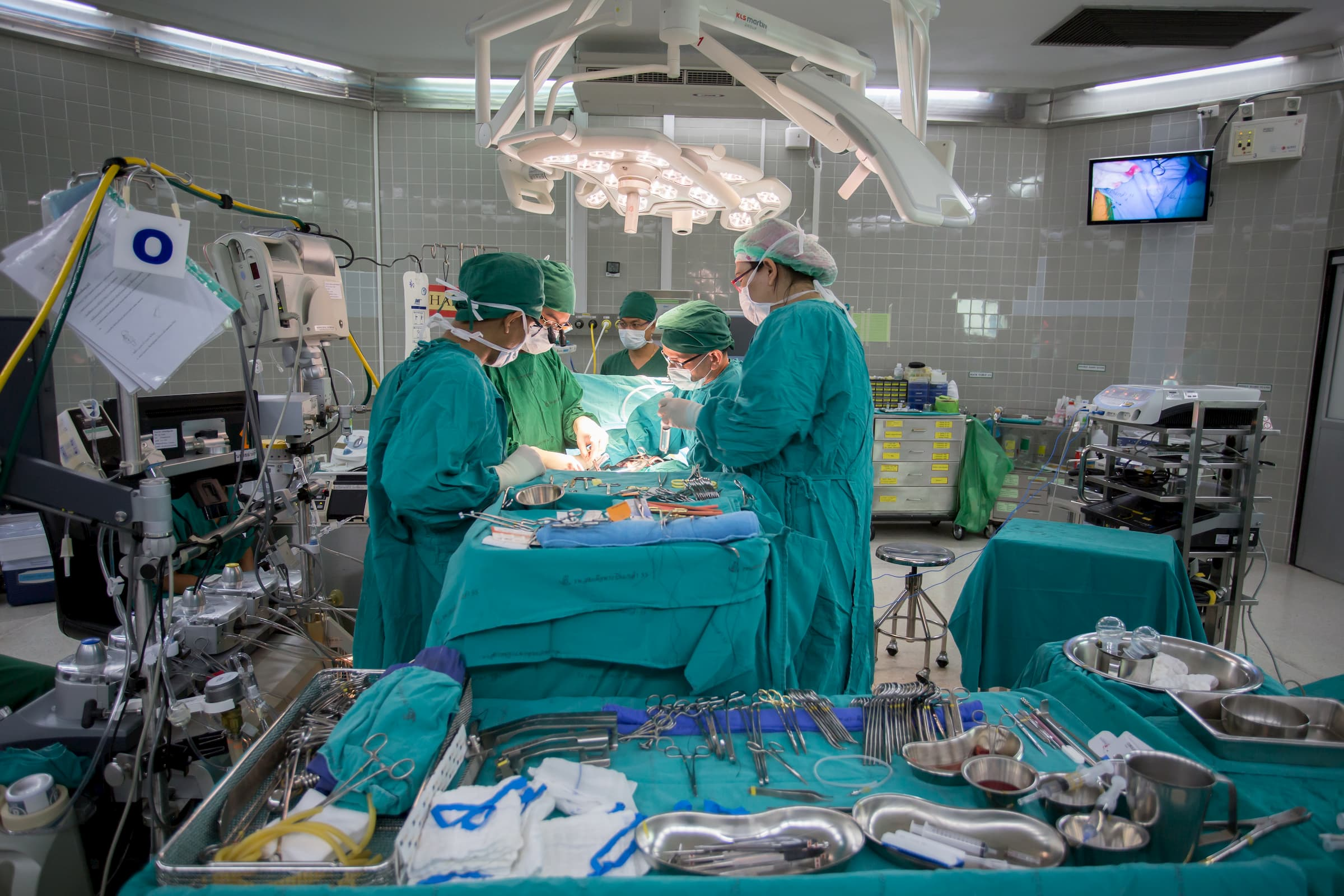 surgery with surgical team in aqua scrubs performing surgery in operating room with medical tools and surgical trays in foreground