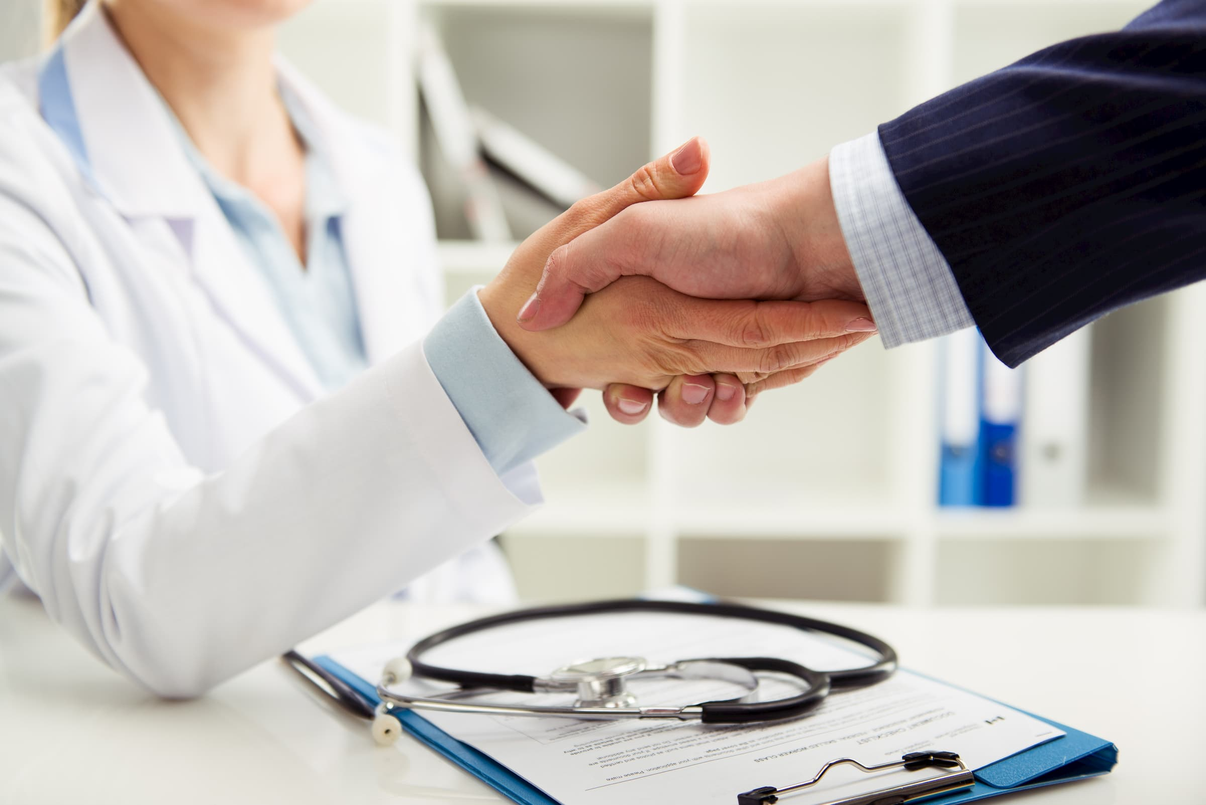 white doctor shaking hands with patient after signing insurance paperwork