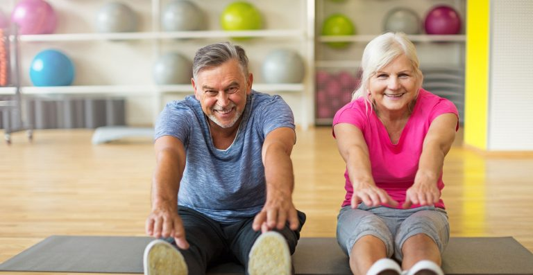 white elderly couple sitting and reaching for toes doing physical therapy and exercising for better health and rehabilitation