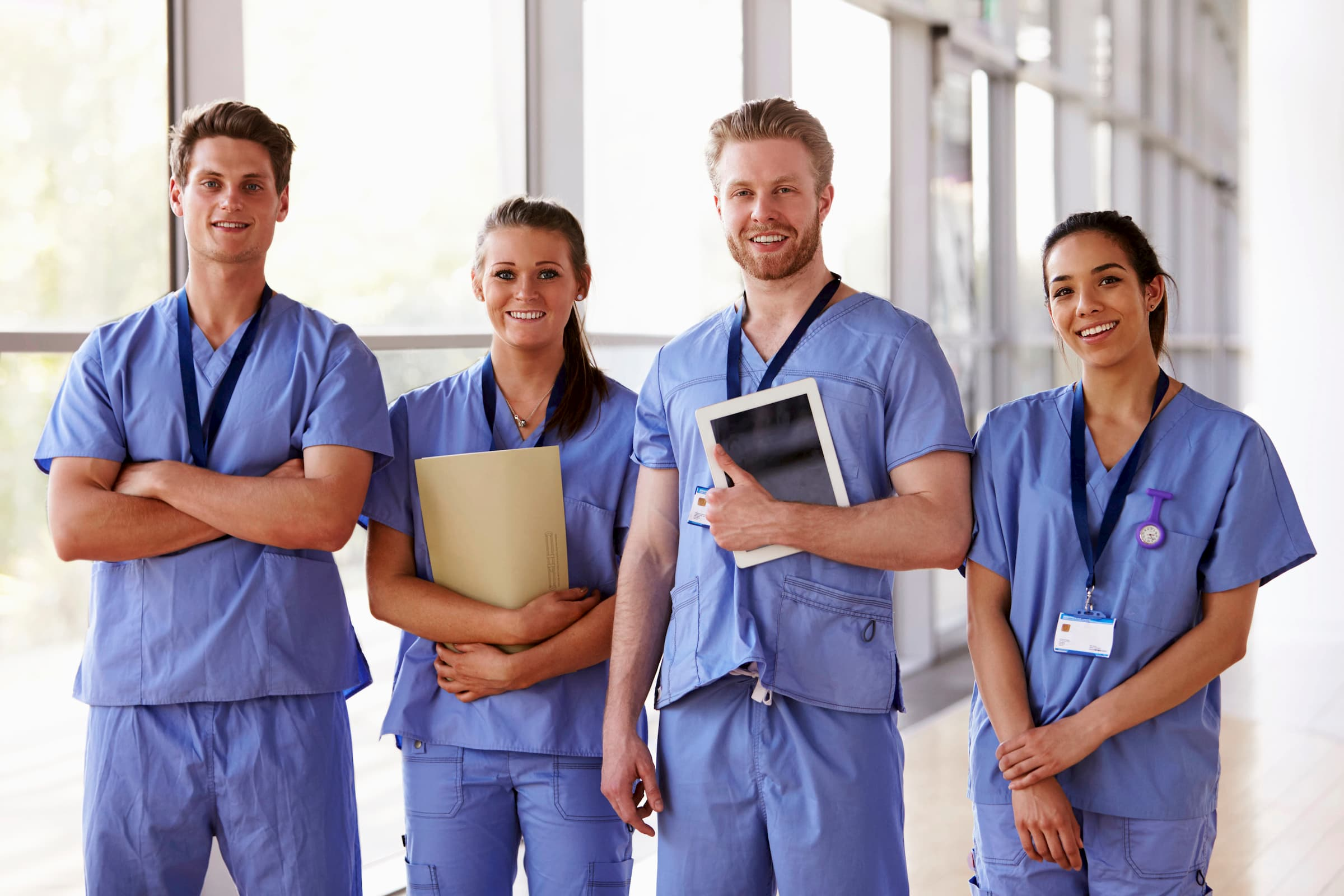 Group of young doctors or nurses in ciel blue scrubs, two men, two women, white and hispanic