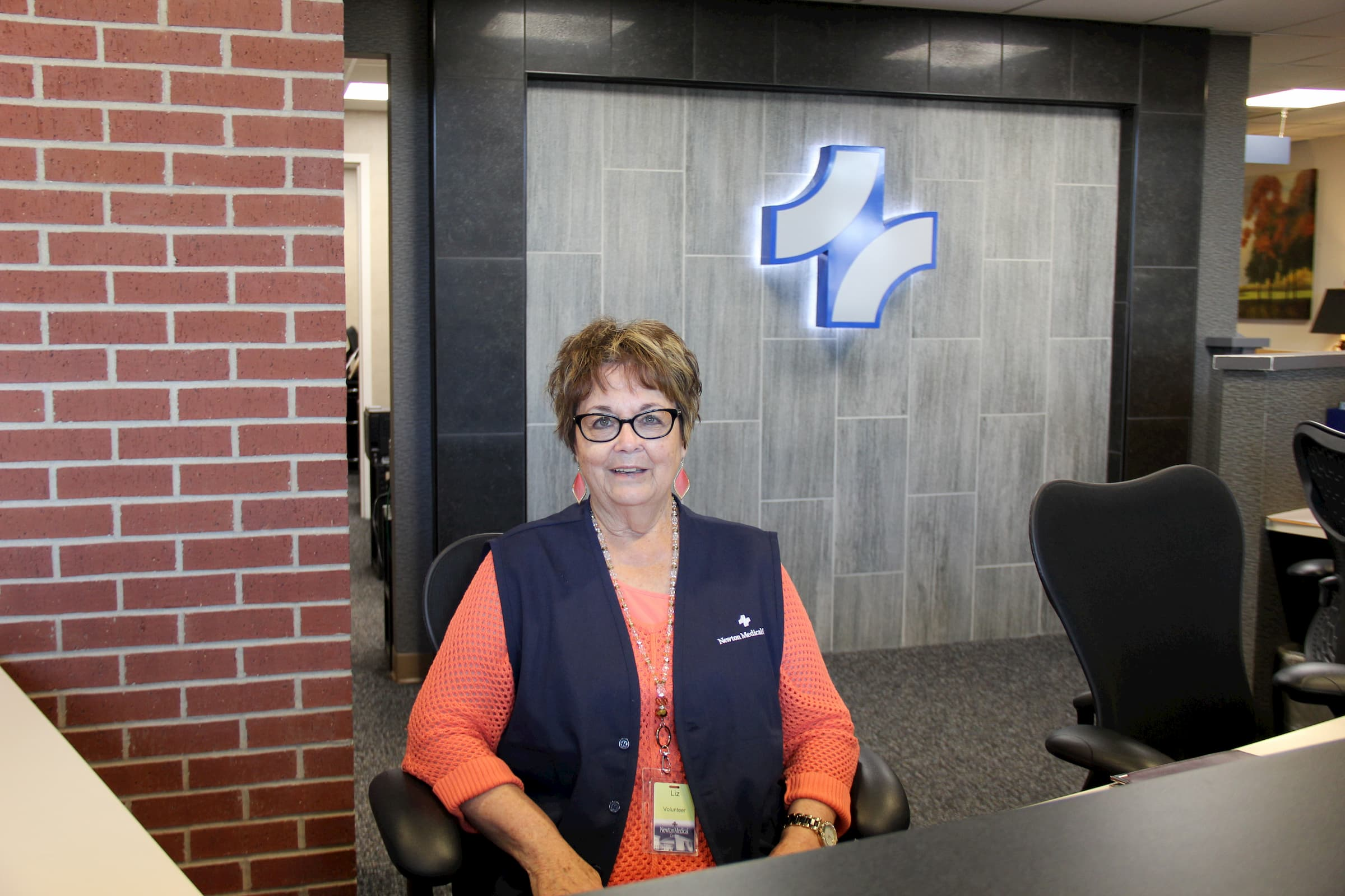 white female volunteer in blue vest sitting at desk