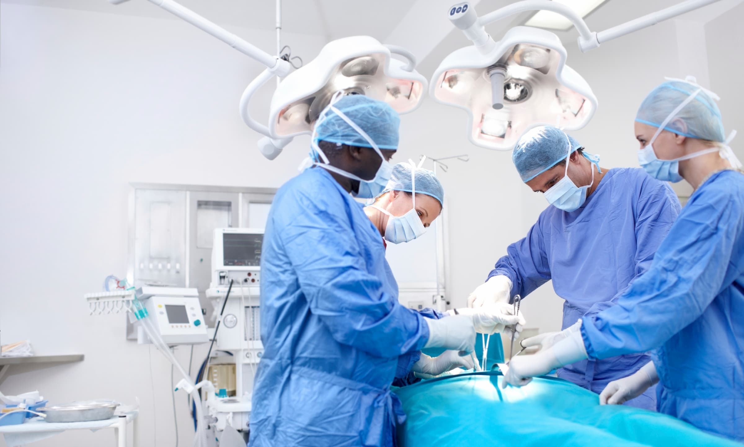 diverse doctors (black, white, hispanic, white) doing surgery in blue scrubs and surgical gear, leaning over patient on the table