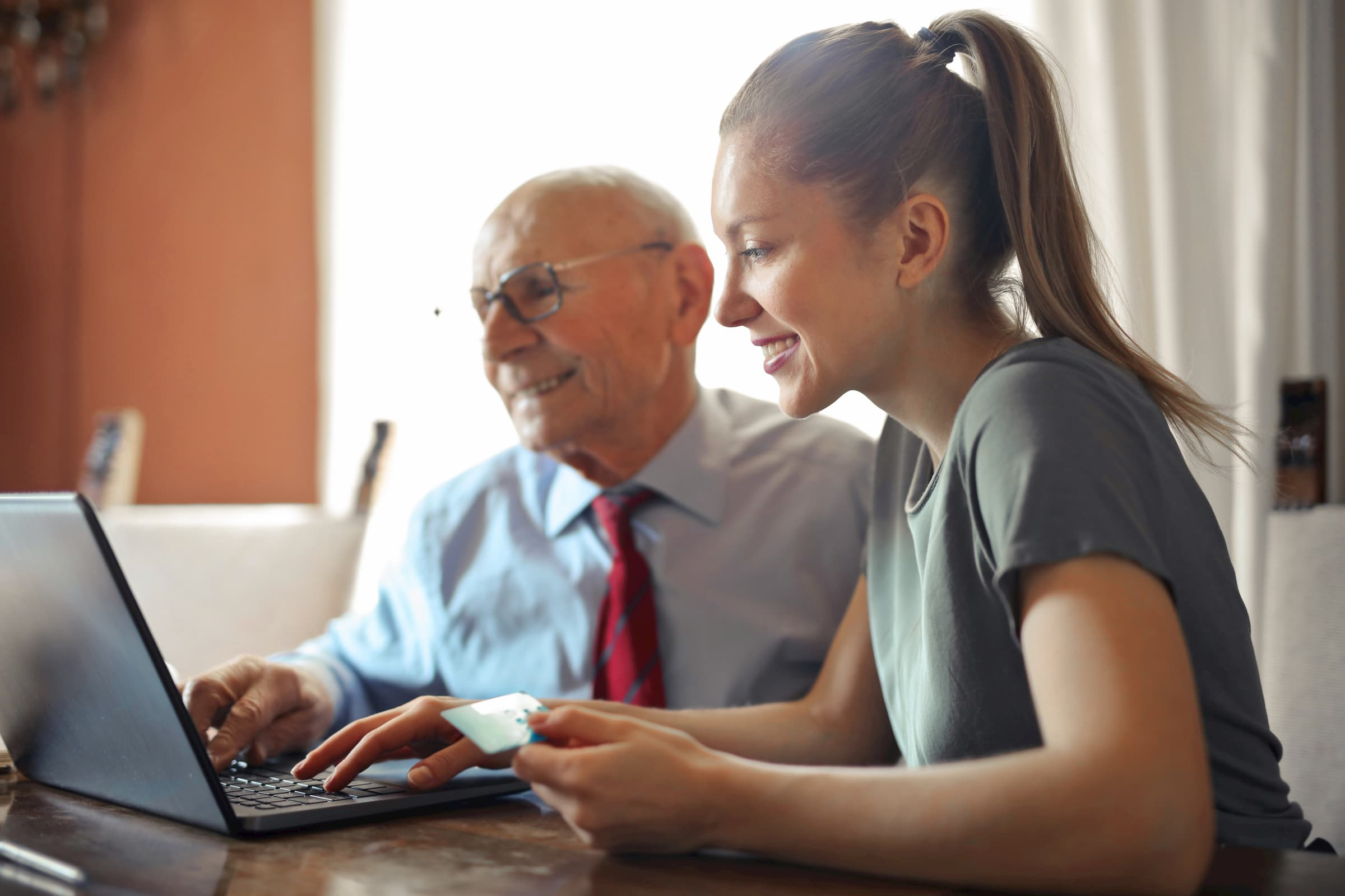 white elderly man and white woman making a payment online with a credit card at a laptop