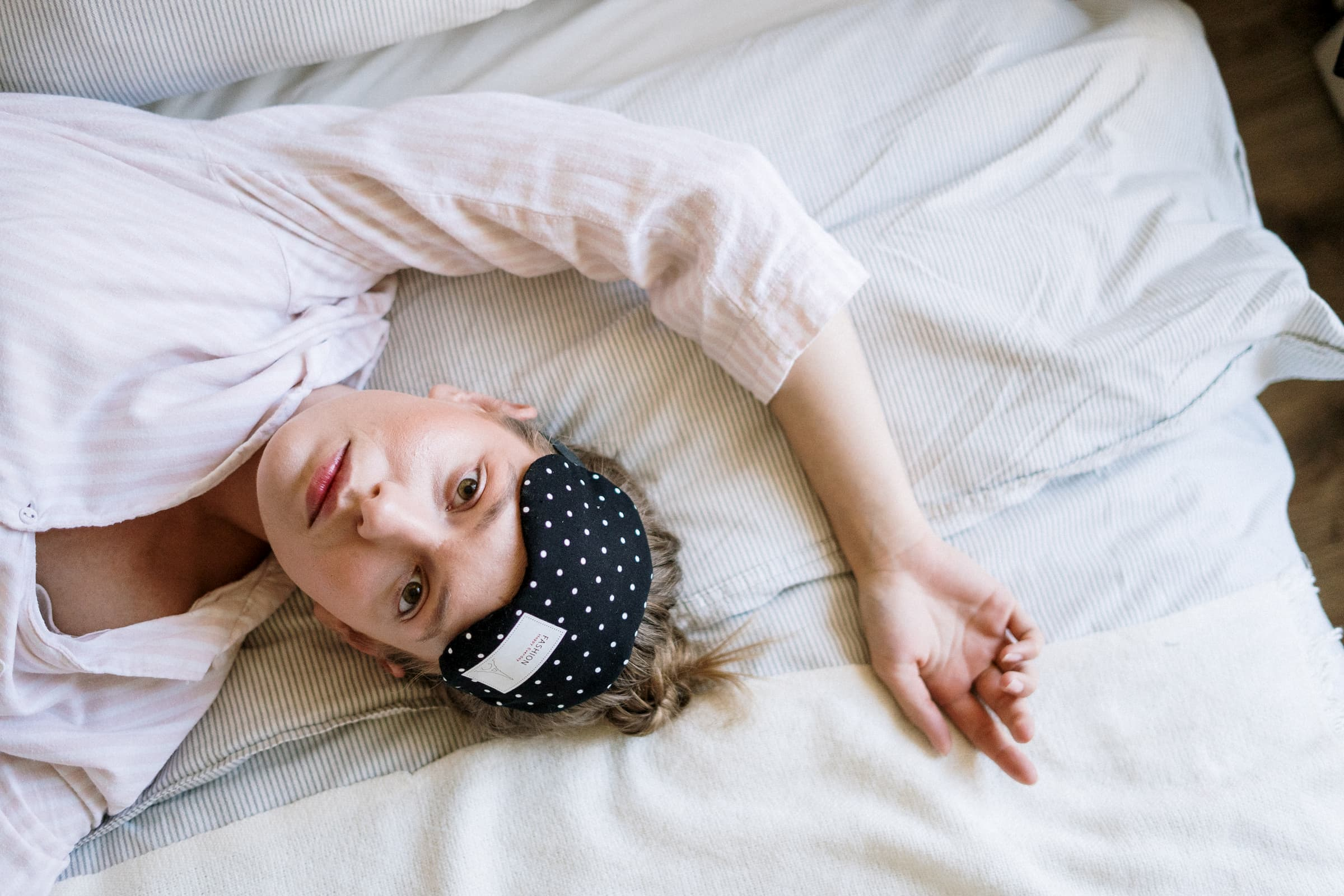 white woman in white shirt laying in bed with sleep mask raised because insomnia can't sleep, sleep disorders, wide awake