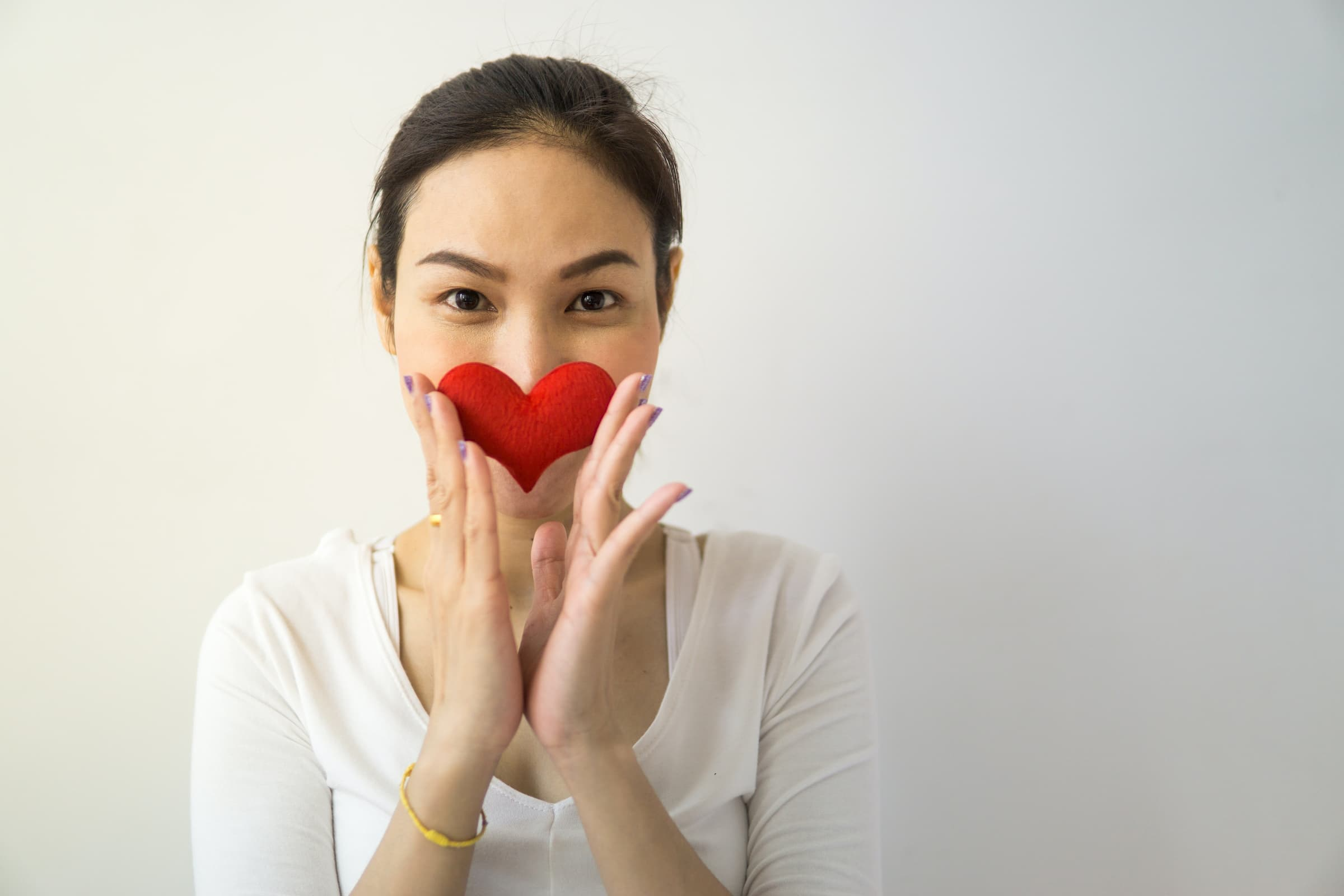 asian woman standing with heart up to nose smiling and asking for donations