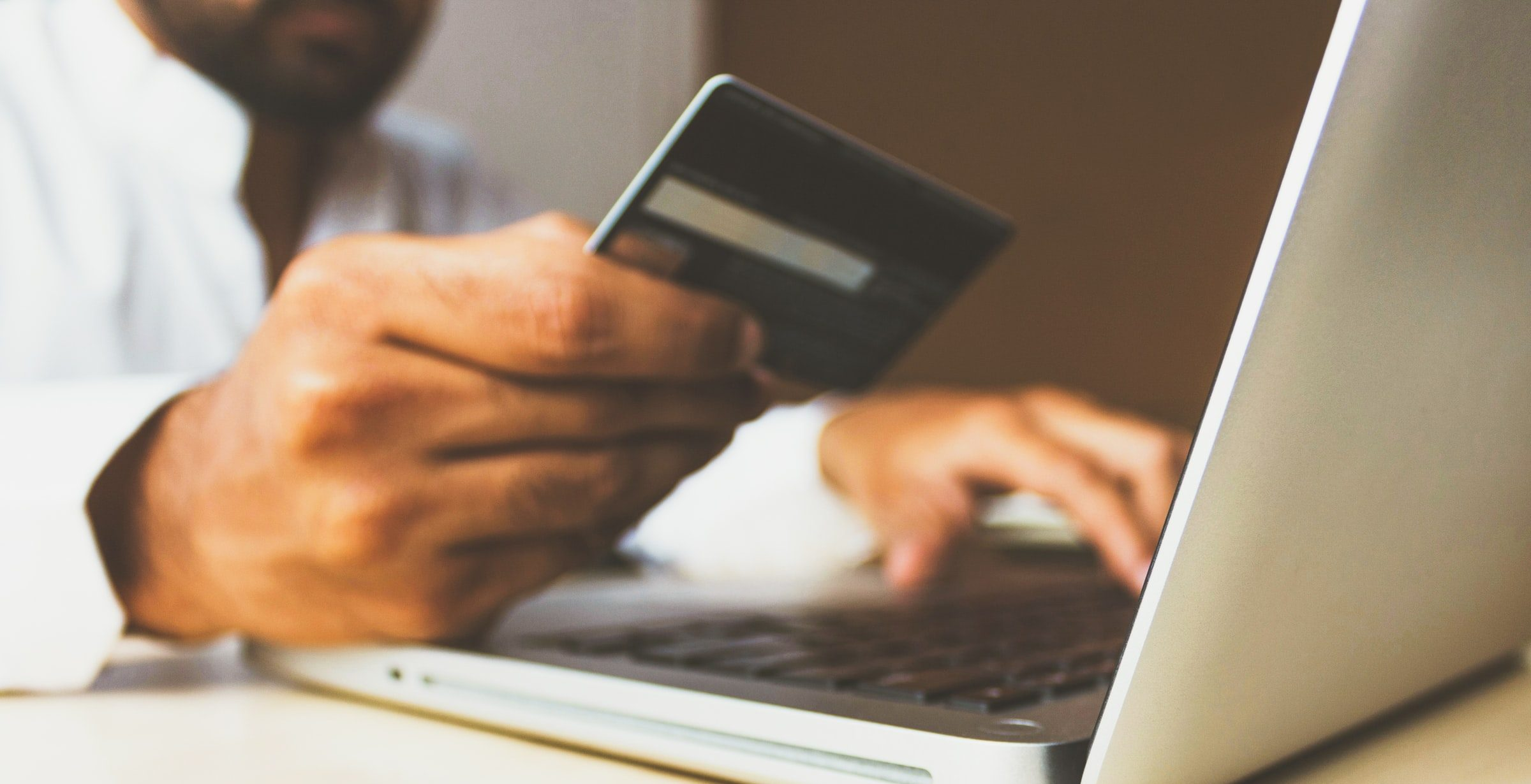 man with credit card in his hand typing in numbers to pay bill online