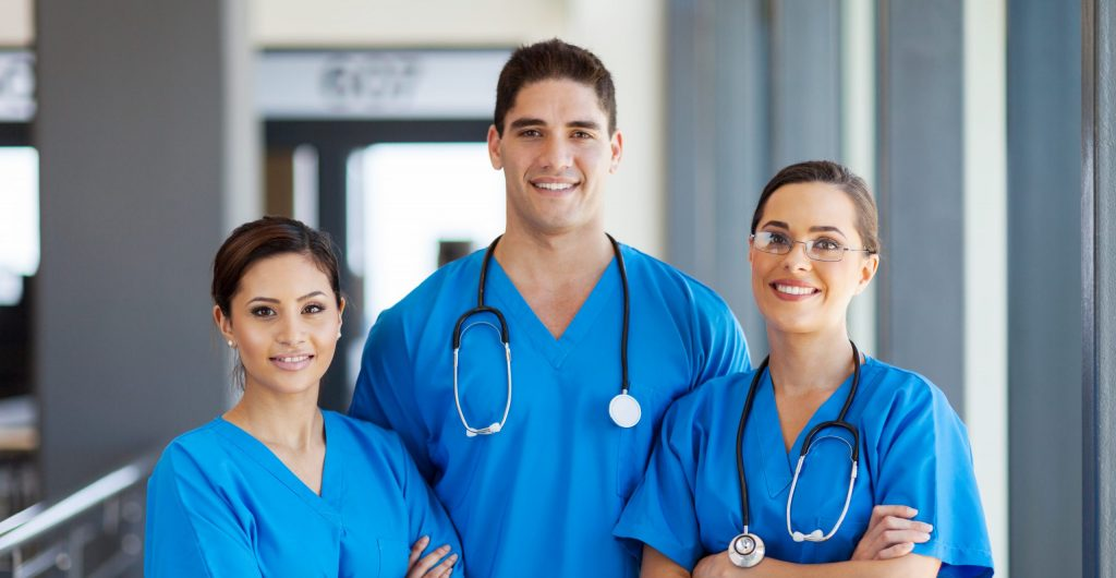diverse group of doctors/nurse in blue scrubs hispanic white and arab