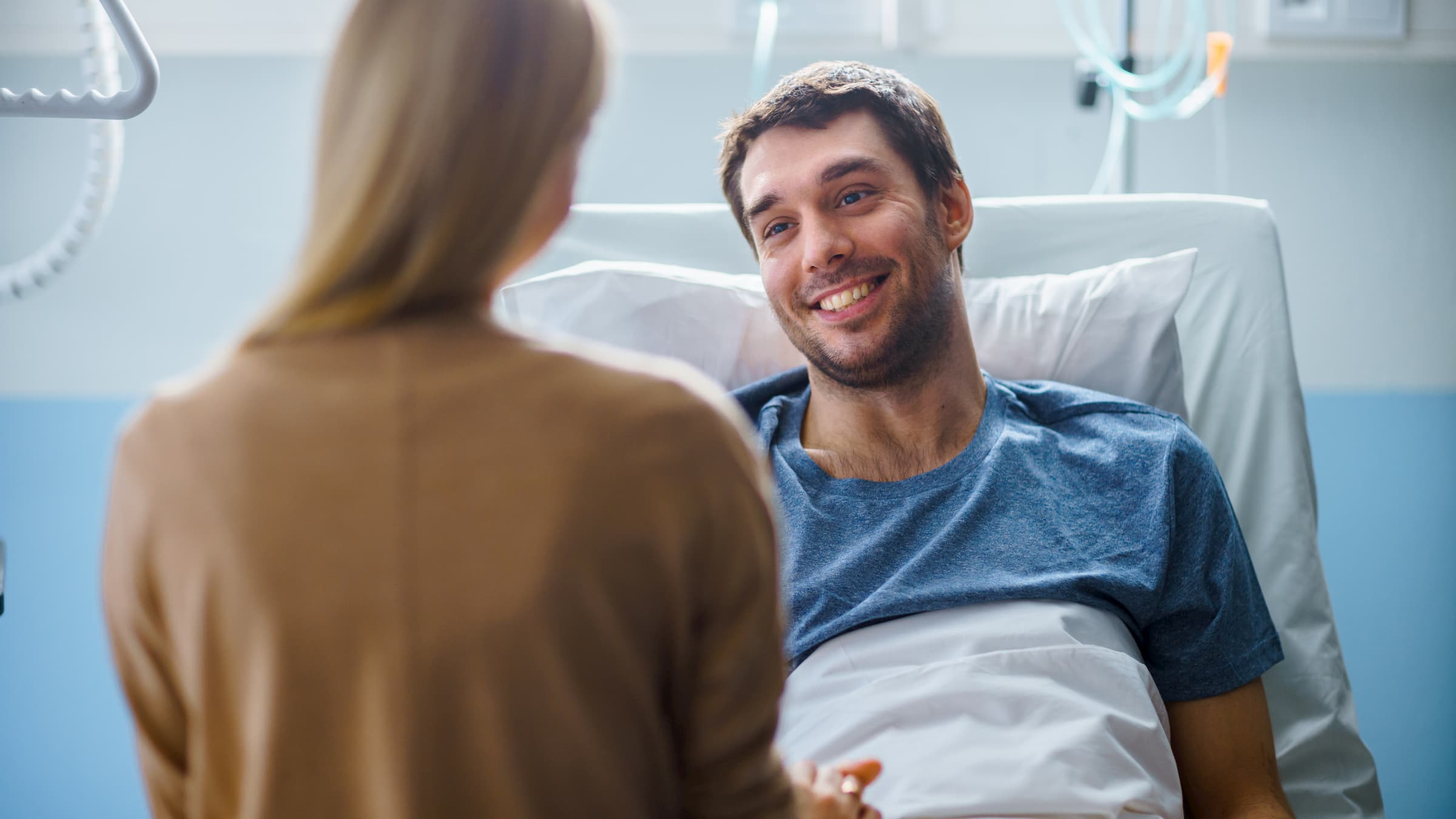 In the Hospital, Man Recovering from Illness Lying in Bed, Loving Wife Visits Him. He is Smiling and Looking at Wife.