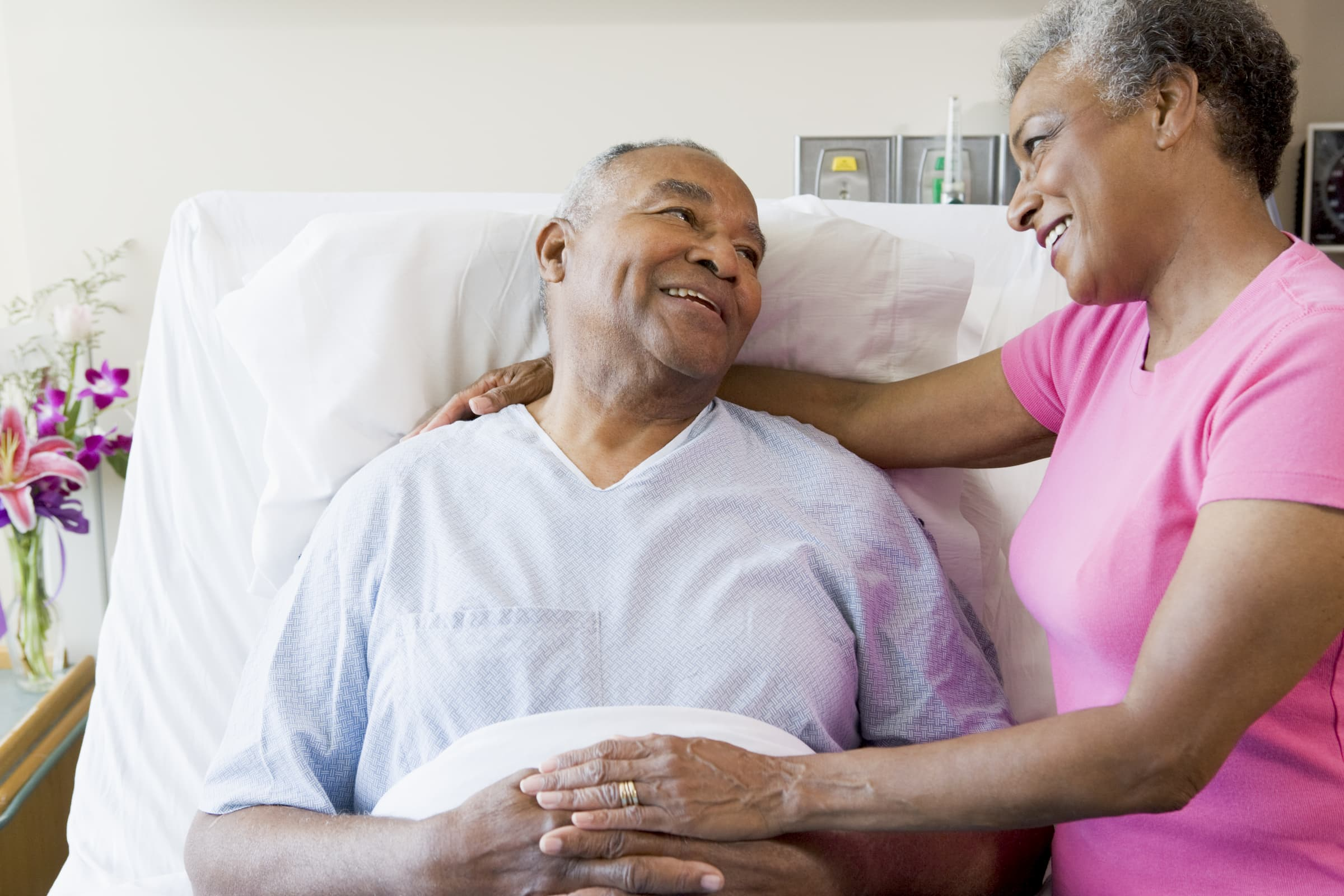 black senior couple in hospital room. black woman visiting husband in hospital during visiting hours