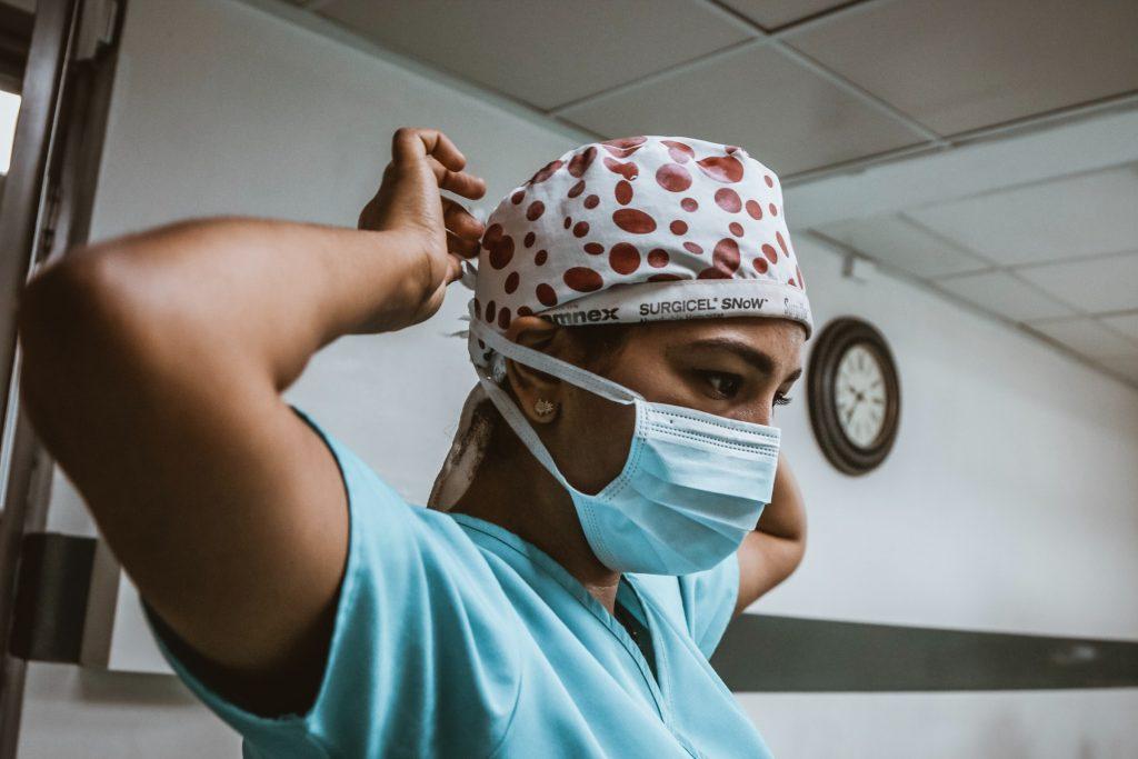 hispanic nurse putting on mask