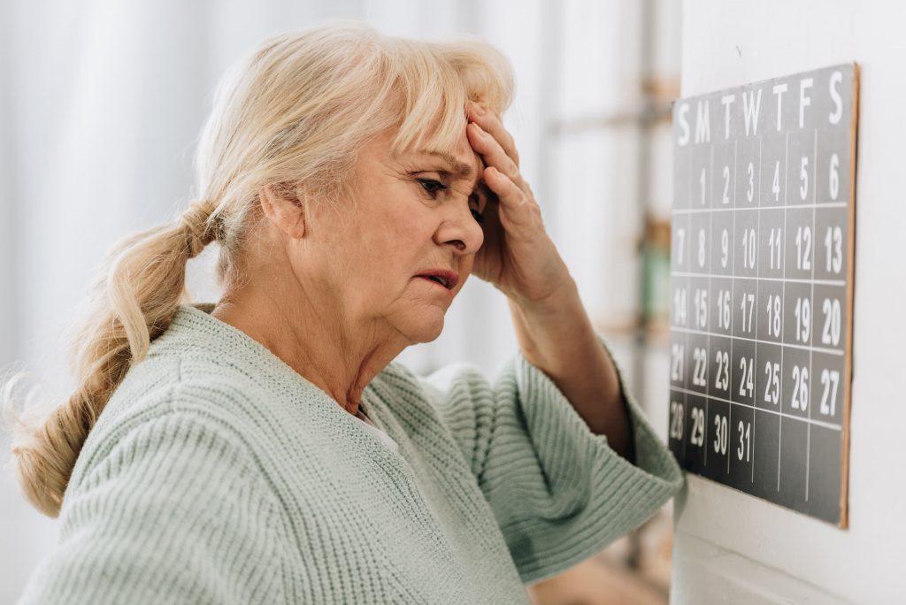 white woman holding head while looking at neurology brain scans - dementia, memory loss, neurology care