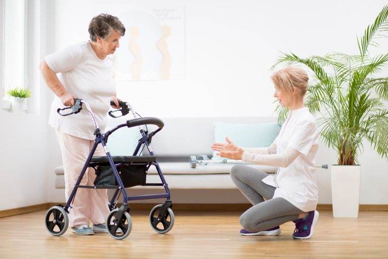 white senior woman learning to walk with rollator during physical therapy