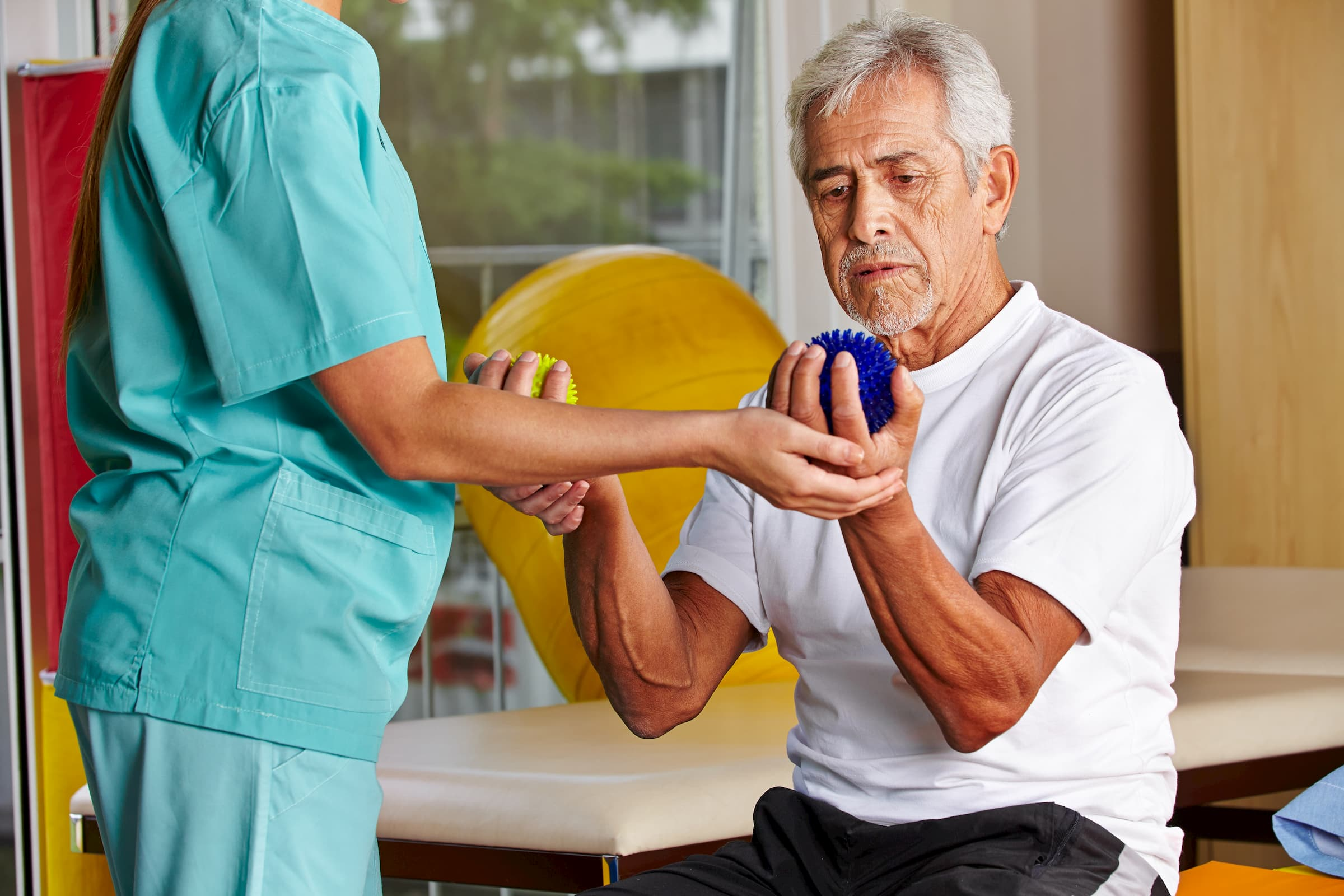 hispanic man doing occupational therapy with balls in hand