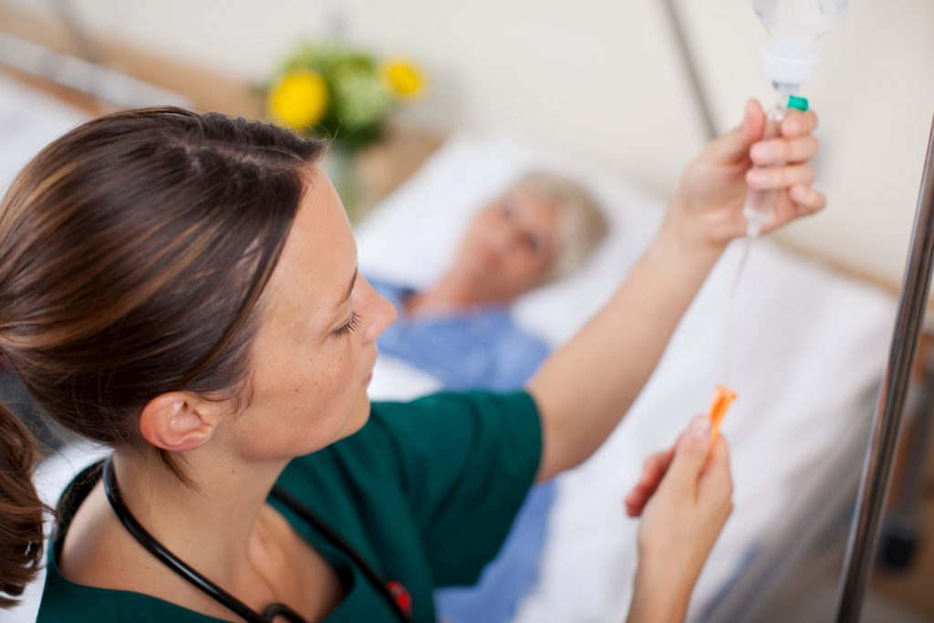 nurse putting medicine in IV for elderly white patient in infusion center stock photo