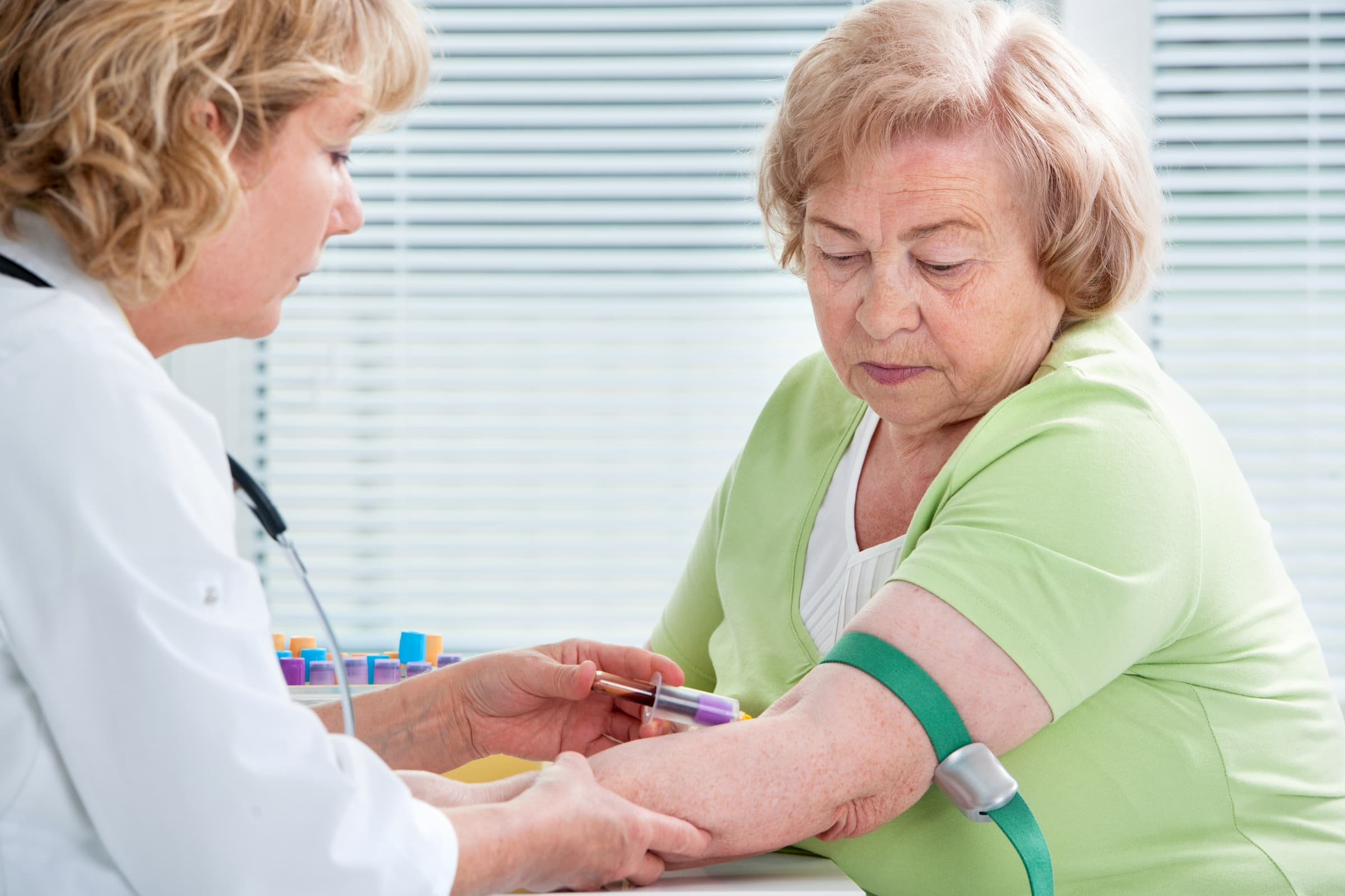 white older senior woman getting blood drawn for medical purposes with white nurse