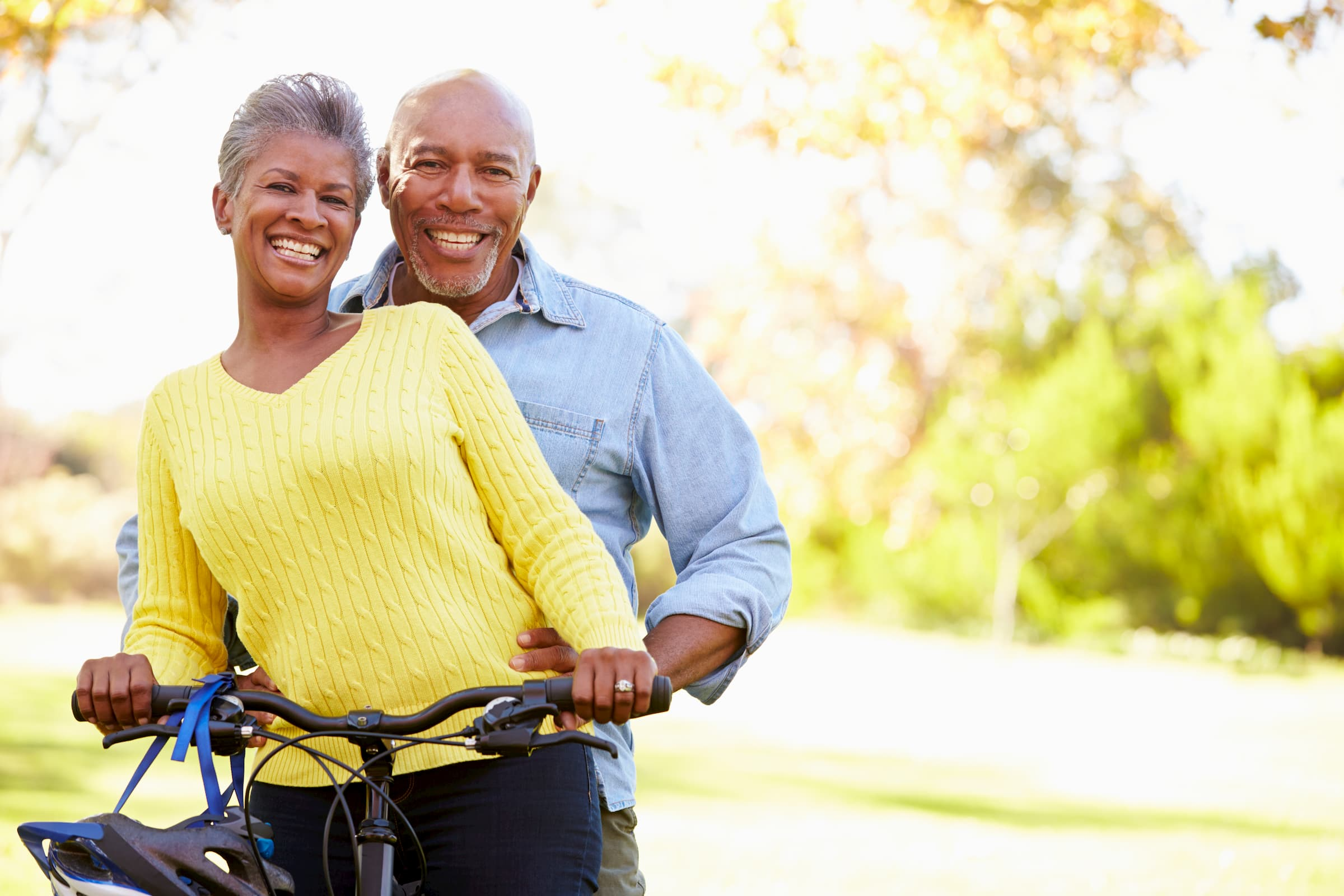 black senior couple in yellow and blue shirt standing outside on bicycle