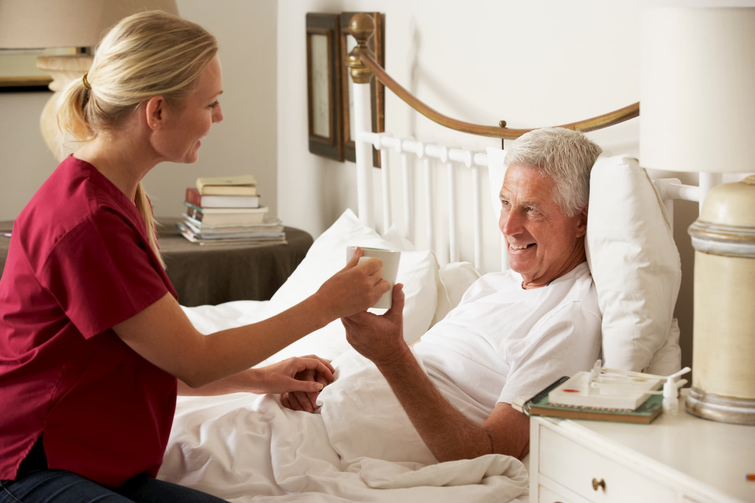 white caregiver helping white man laying in bed with getting a drink of coffee