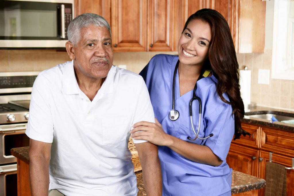 hispanic man in white shirt being helped by a hispanic nurse for home health care and private duty
