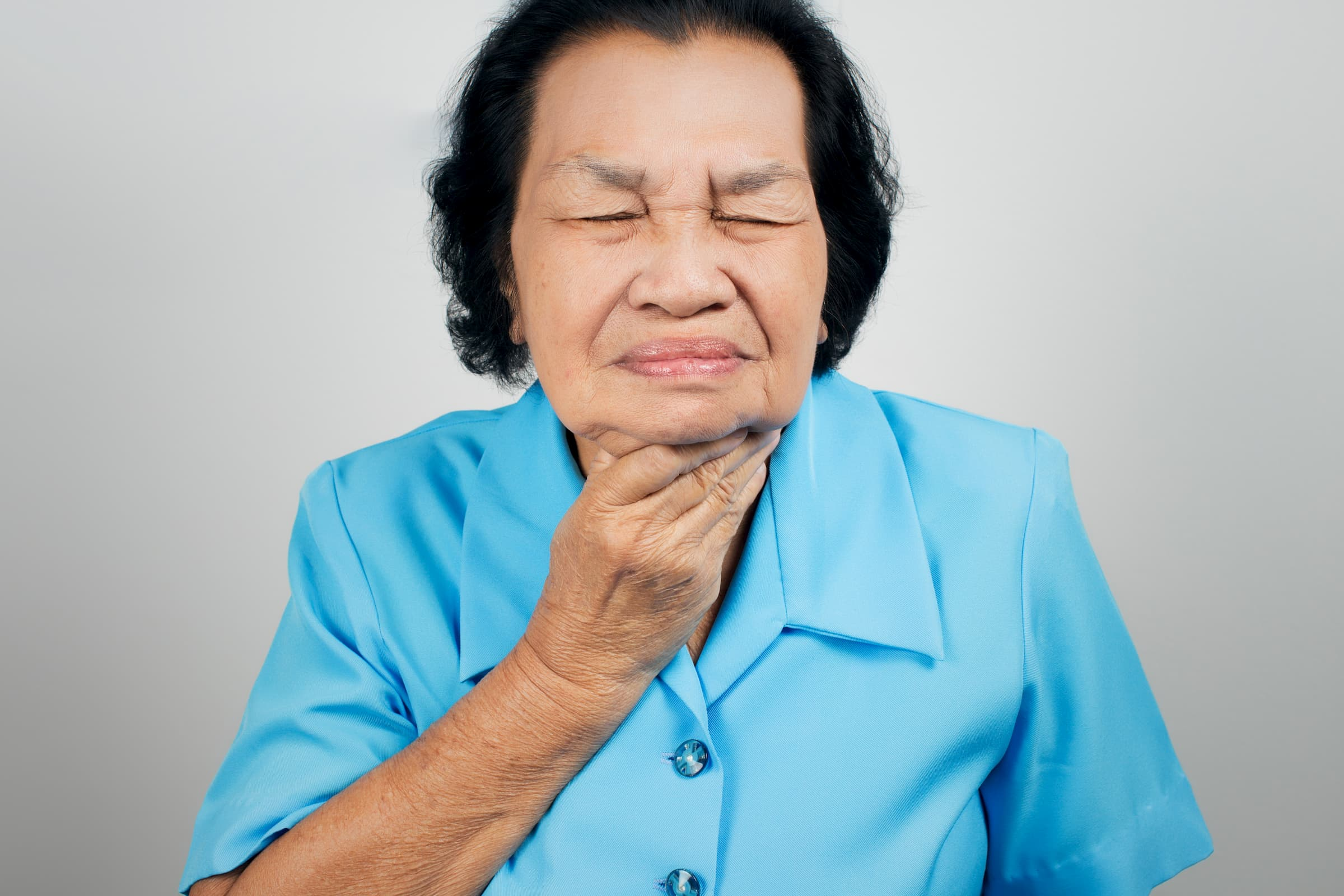 senior asian woman clutching throat for swallowing speech therapy representation