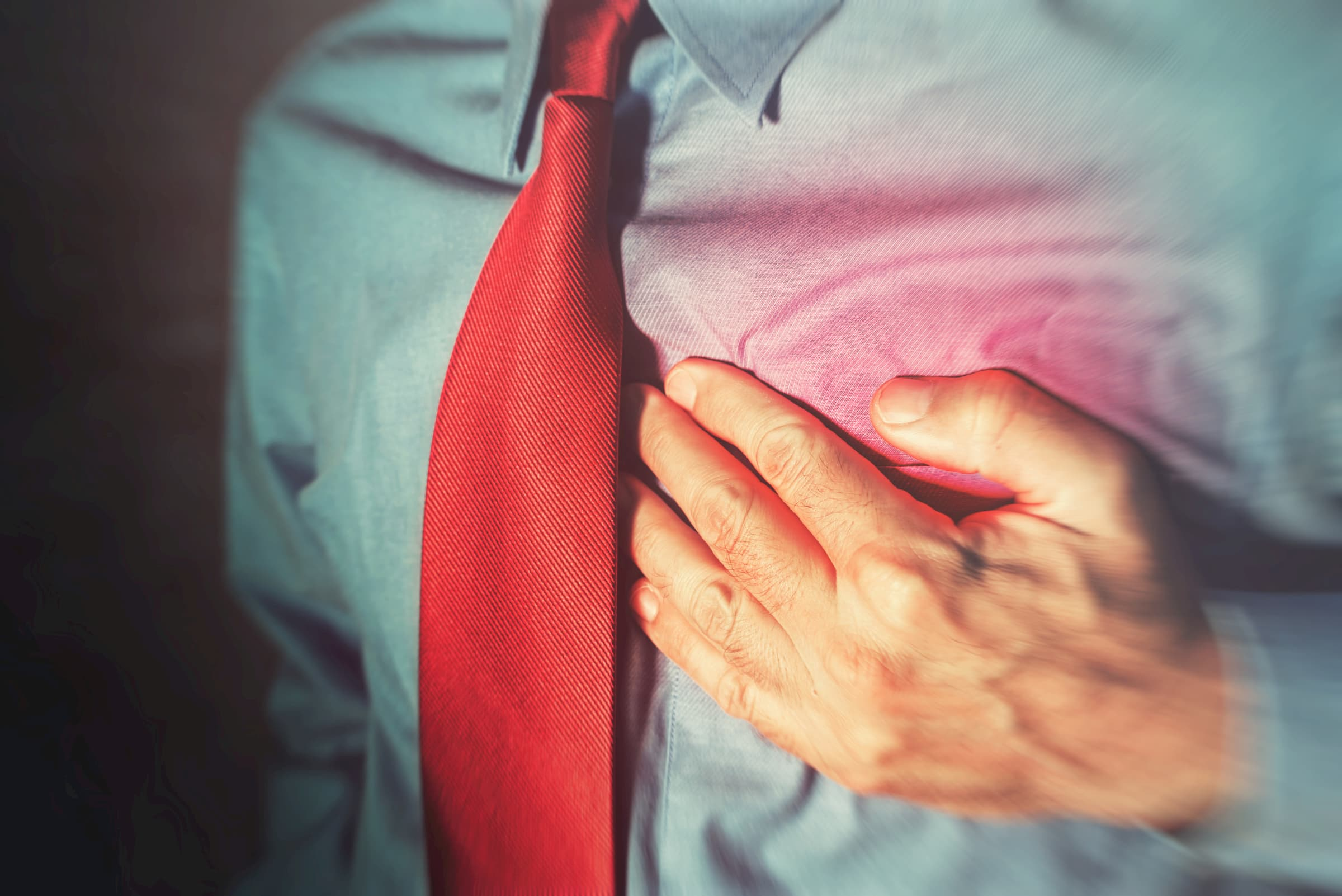 man in blue dress shirt with red tie clenching chest showing heart attack