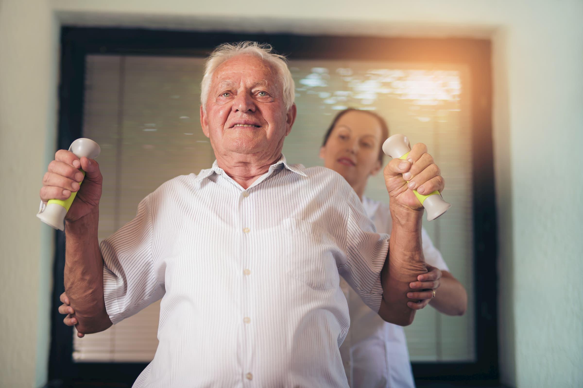 elderly white man lifting weights with nurse therapist