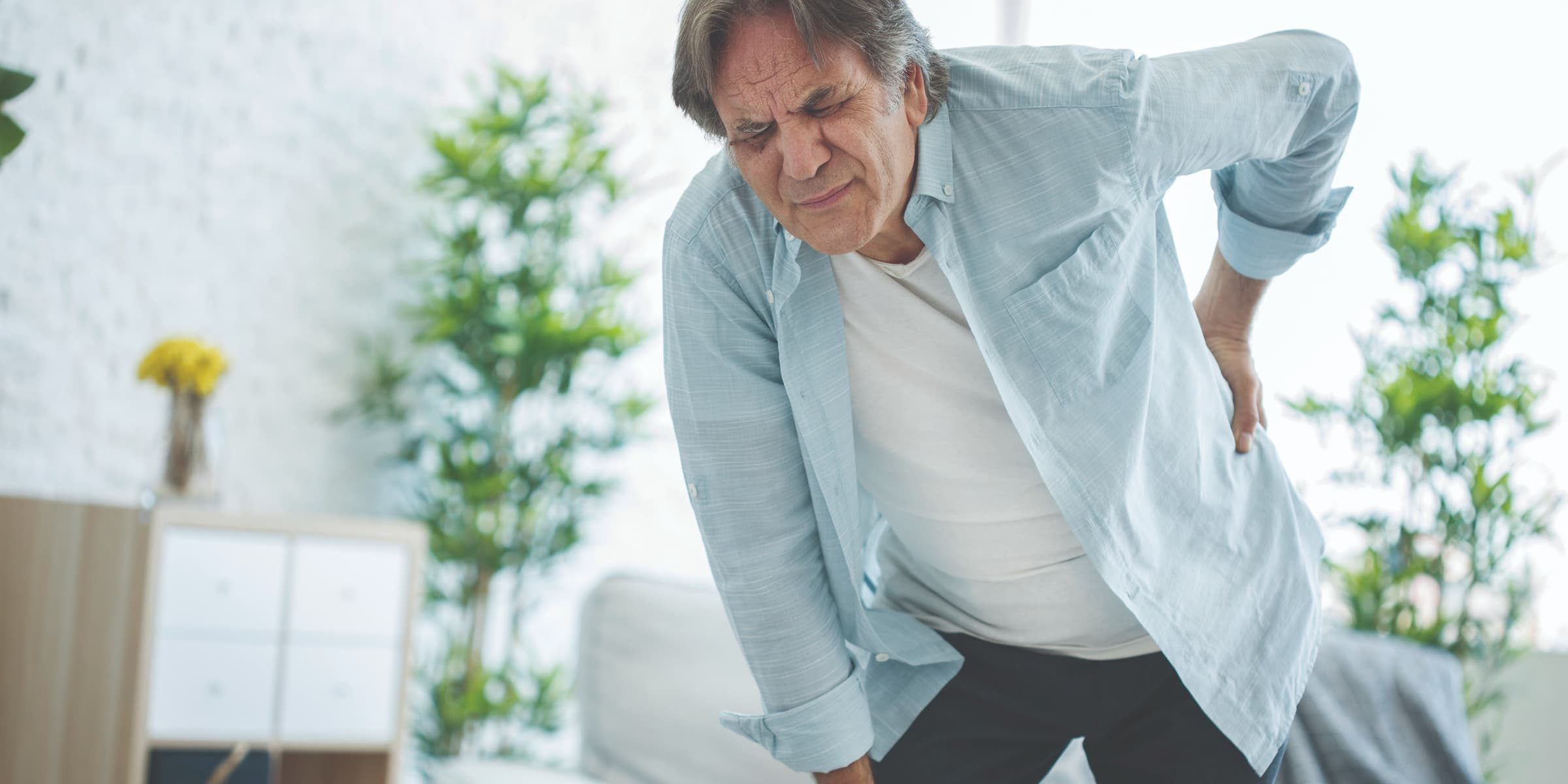 senior white man bent over in pain because of back pain with grimace on face