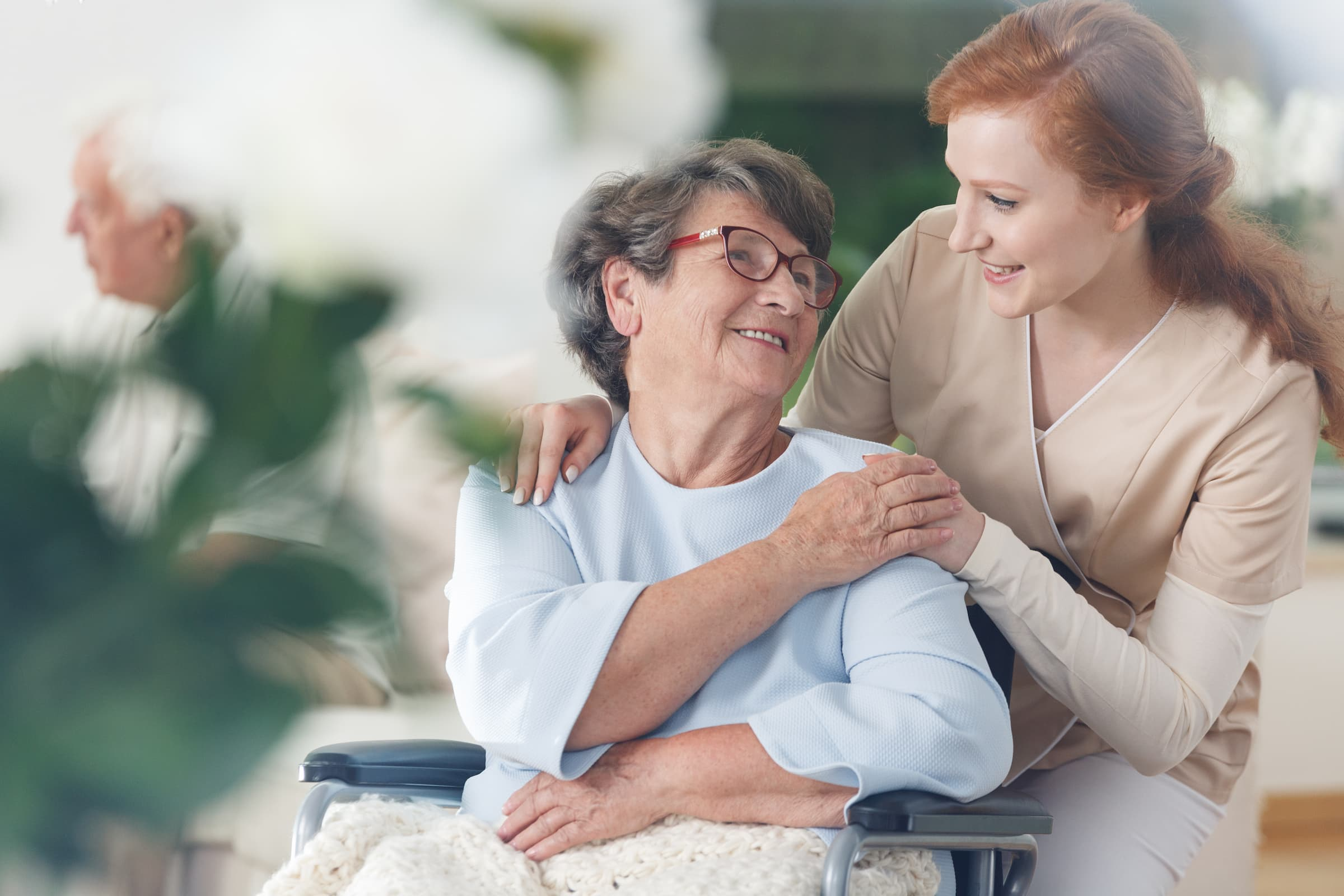 old woman looking up smiling at young nurse who has hand on her shoulder in wheelchair