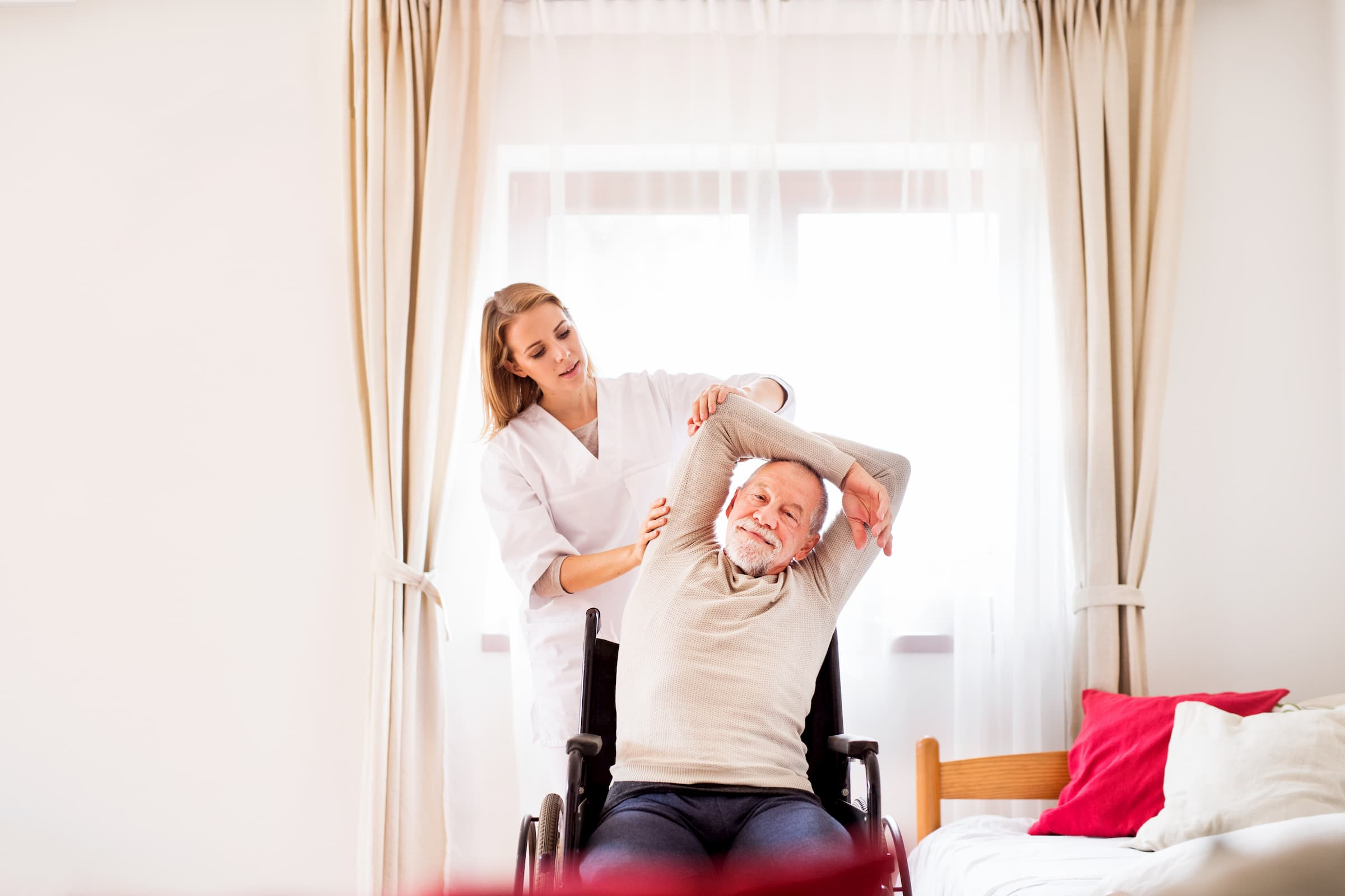 white nurse helping white senior man stretch during inpatient rehab while in wheelchair in patient room at hospital facility