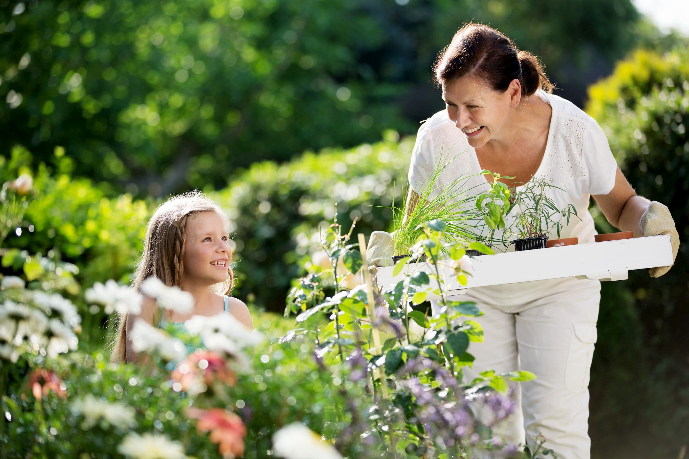 young white girl and elderly white woman working in garden outside
