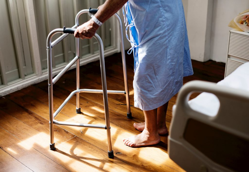 older senior man walking with walker in hospital gown in hospital room - stock image