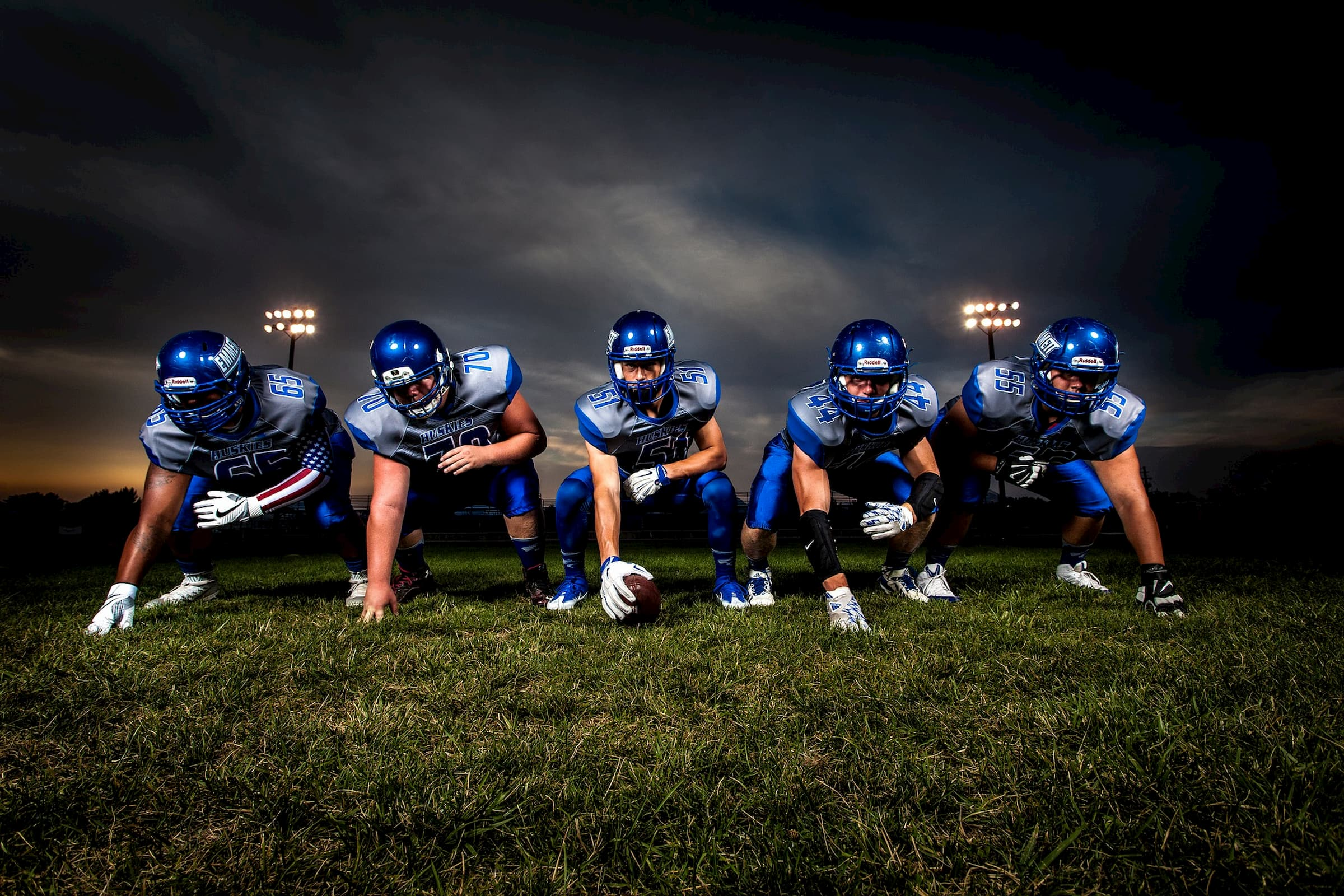 group of football players on the line in full pads wearing blue uniforms and helmets on dark grass with dark sky behind them