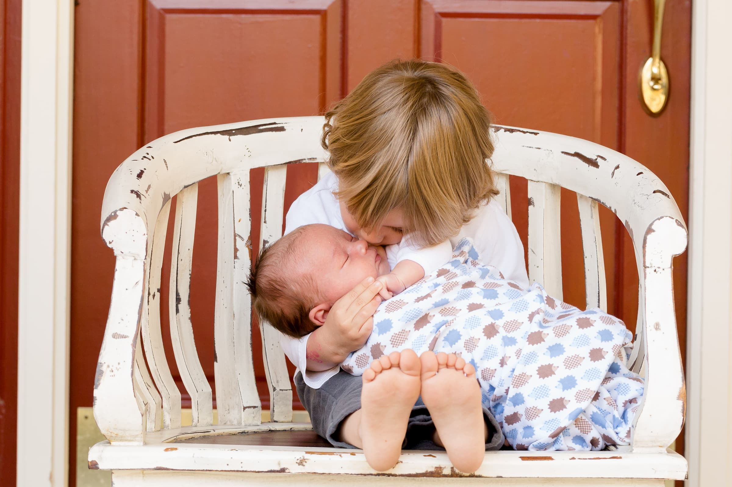 older brother toddler holding newborn baby brother sitting on white chair in front of red door