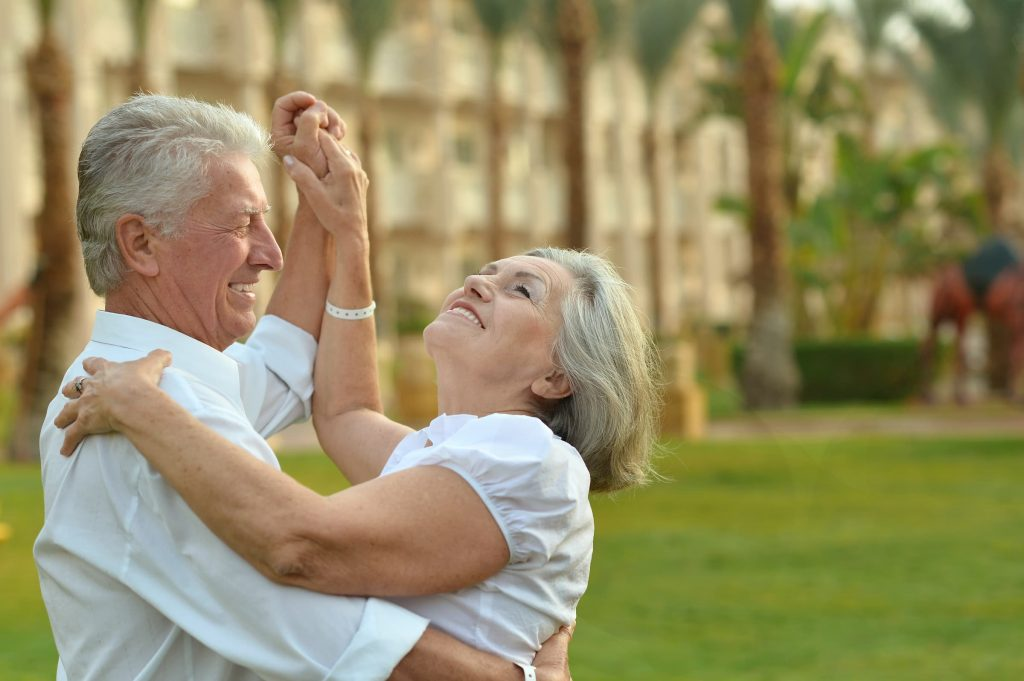 senior white man and woman in white shirts dancing outside on vacation