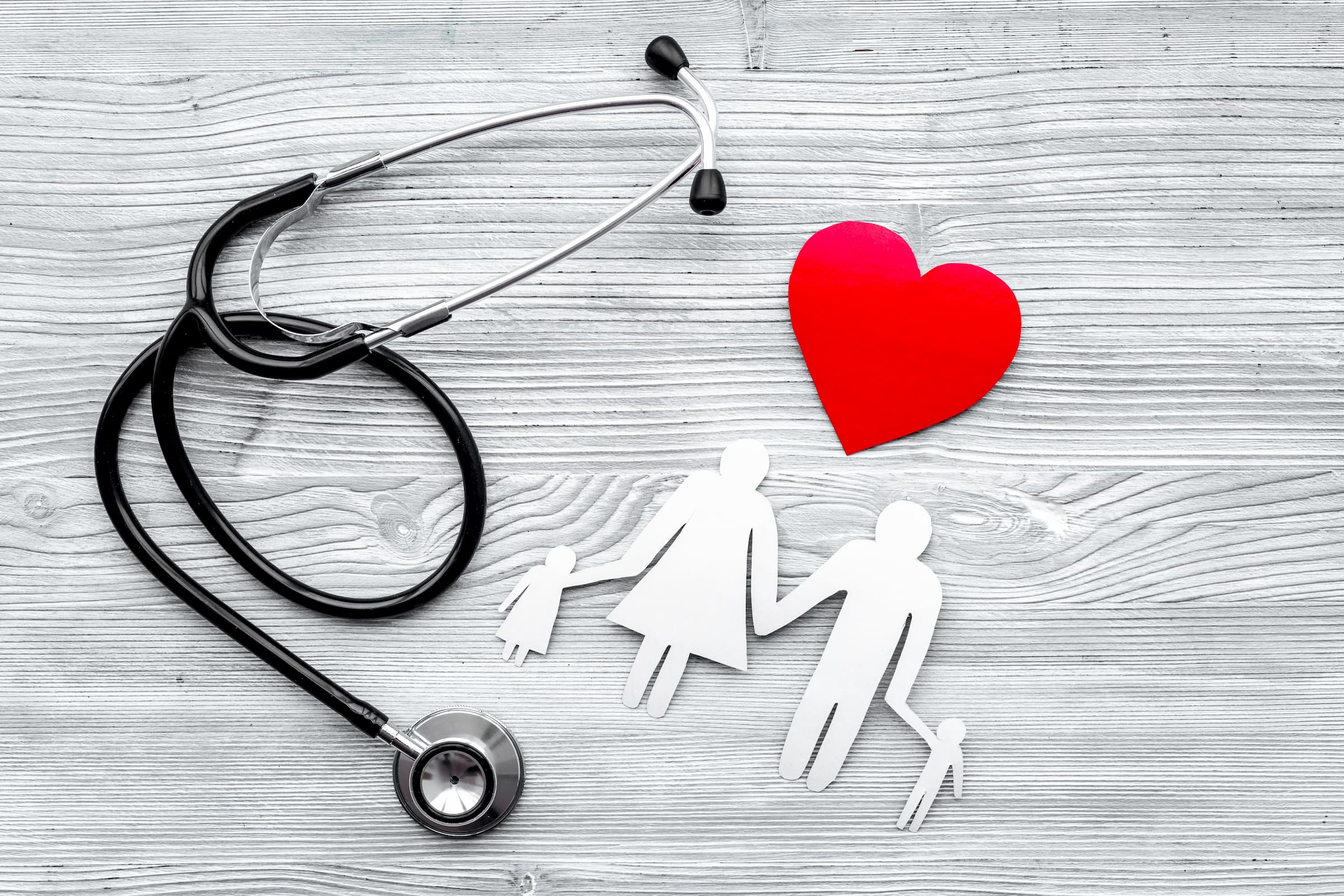 gray background with black stethoscope, white paper family with child female woman male man and another child and heart above them to show community health needs assessment; stock photo