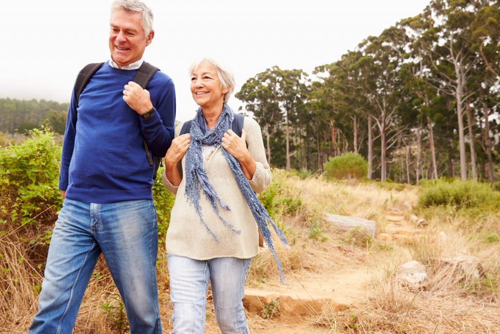 older couple hiking with backpacks walking