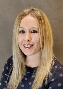 headshot of liz wilson elizabeth wilson in dark blue shirt with polka dots smiling
