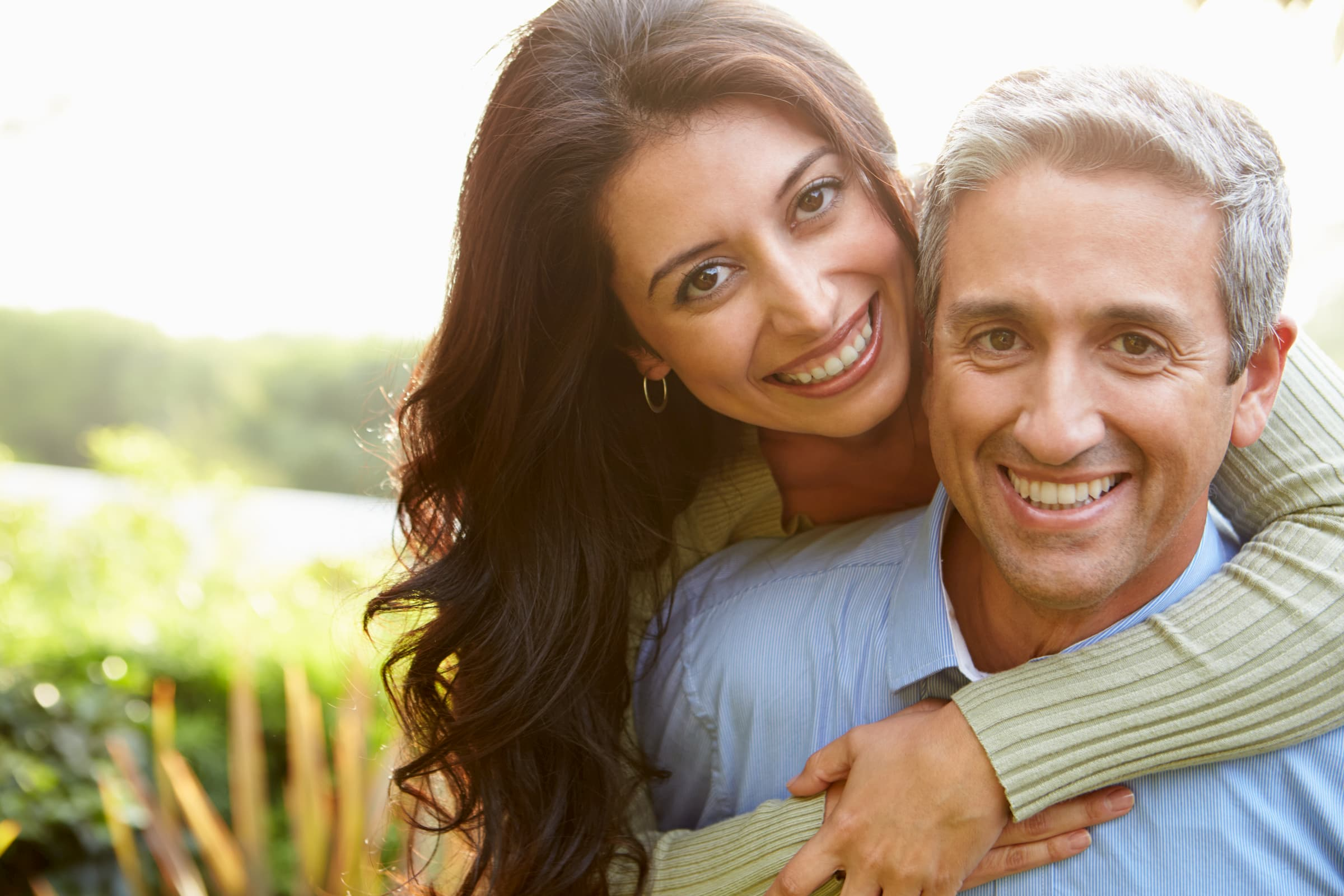 hispanic couple smiling while standing outside woman on man's back