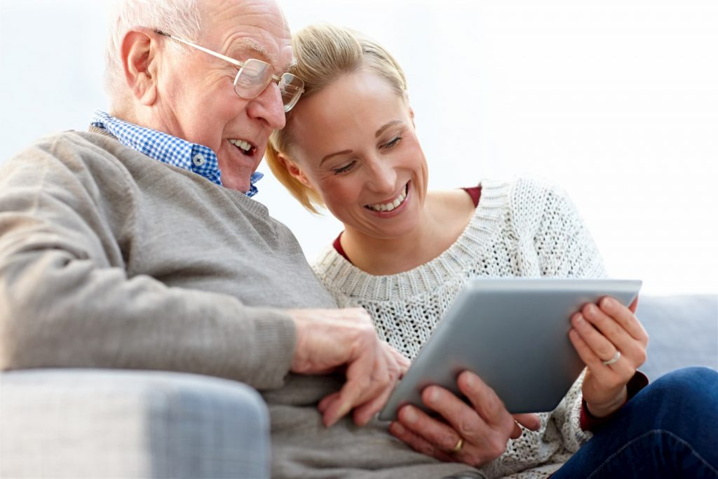 white senior man with white young female woman looking at ipad/tablet for alzheimer's & diabetes support group event