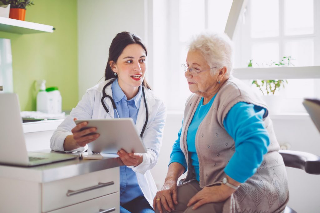 hispanic doctor explaining health forms insurance financial assistance to senior elderly white patient in doctor's office stock photo