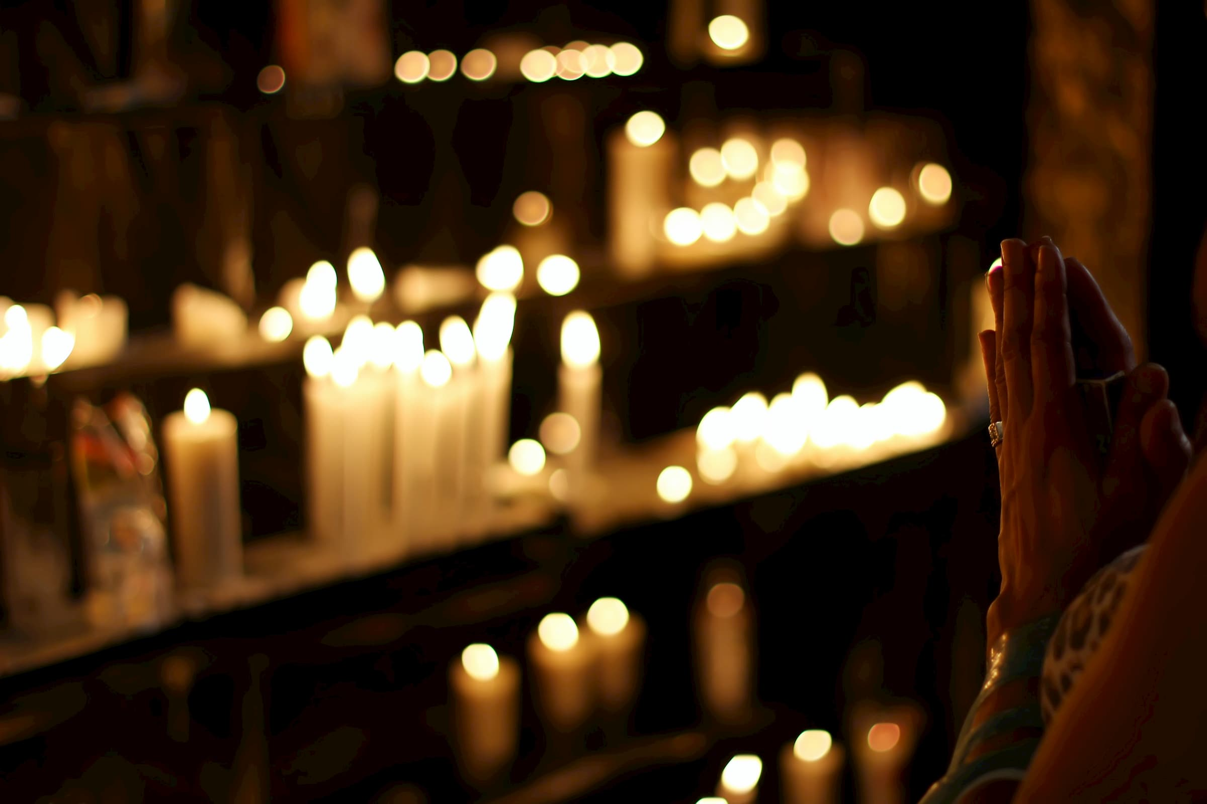 blurred out dark photo of candlelight candle altar and woman praying with prayer hands in the dark