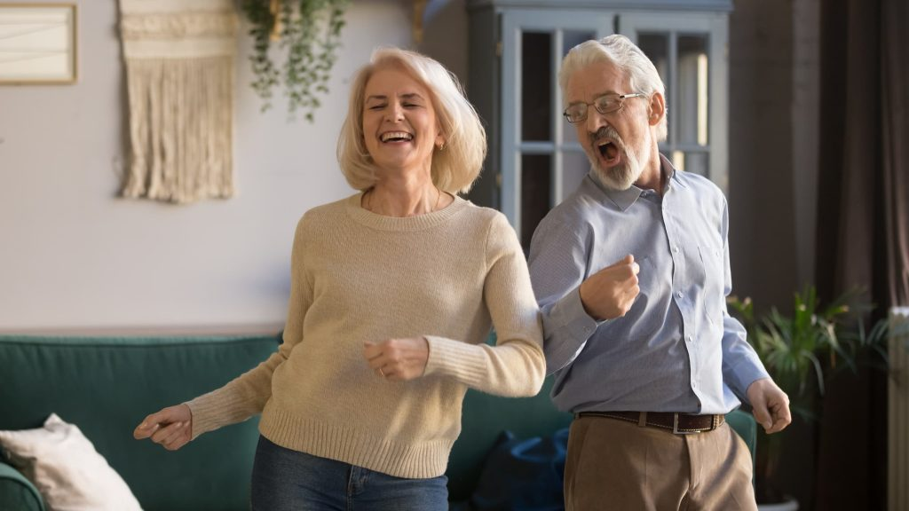white senior couple man and woman dancing in their living room back on your feet light on your feet dancing happy couple
