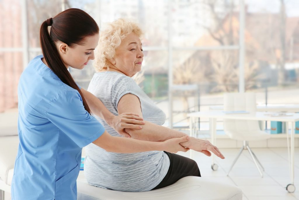 white senior woman and physical therapist occupational therapist working on her elbow joint pain
